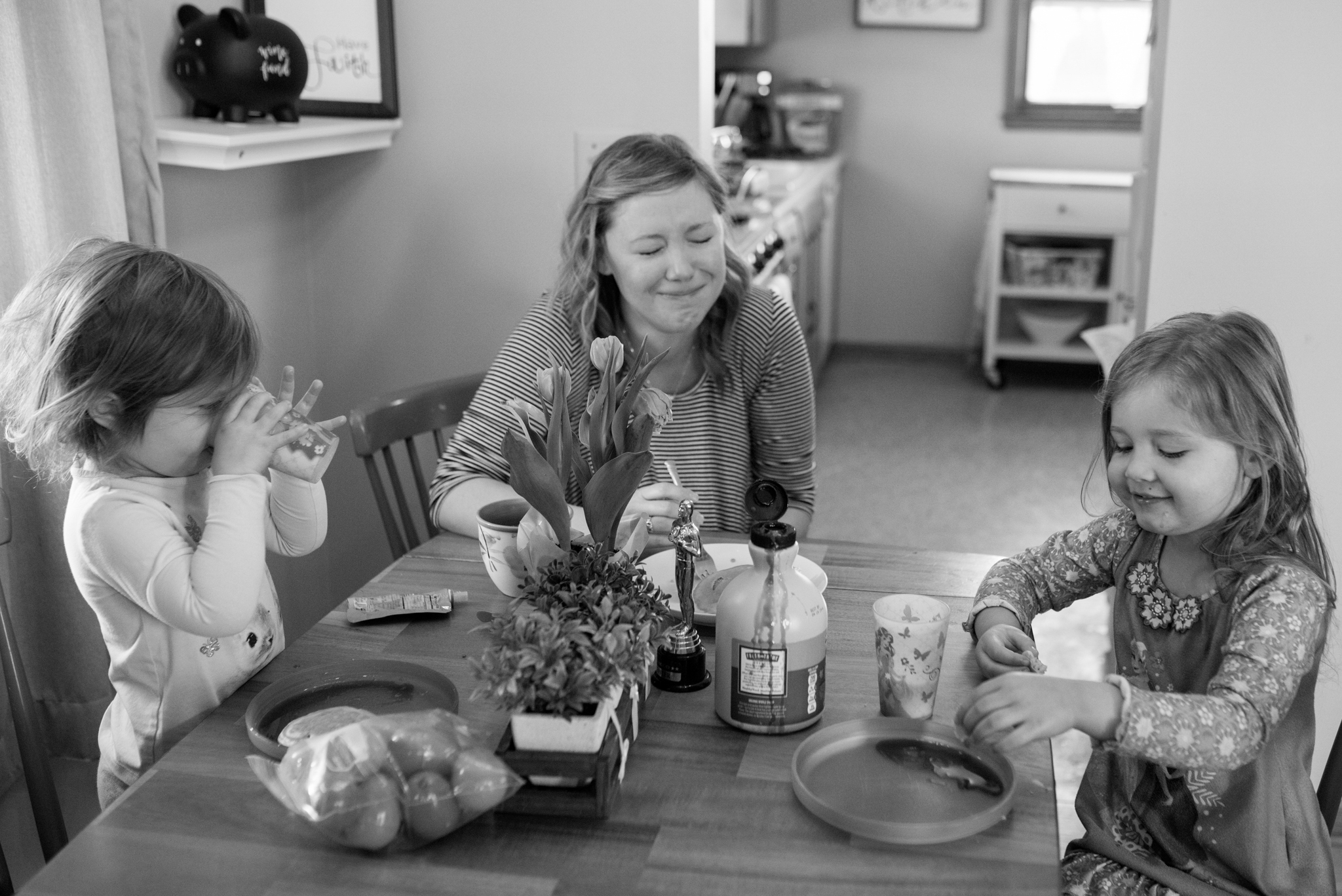 Mom and daughters at kitchen table, mom laughing