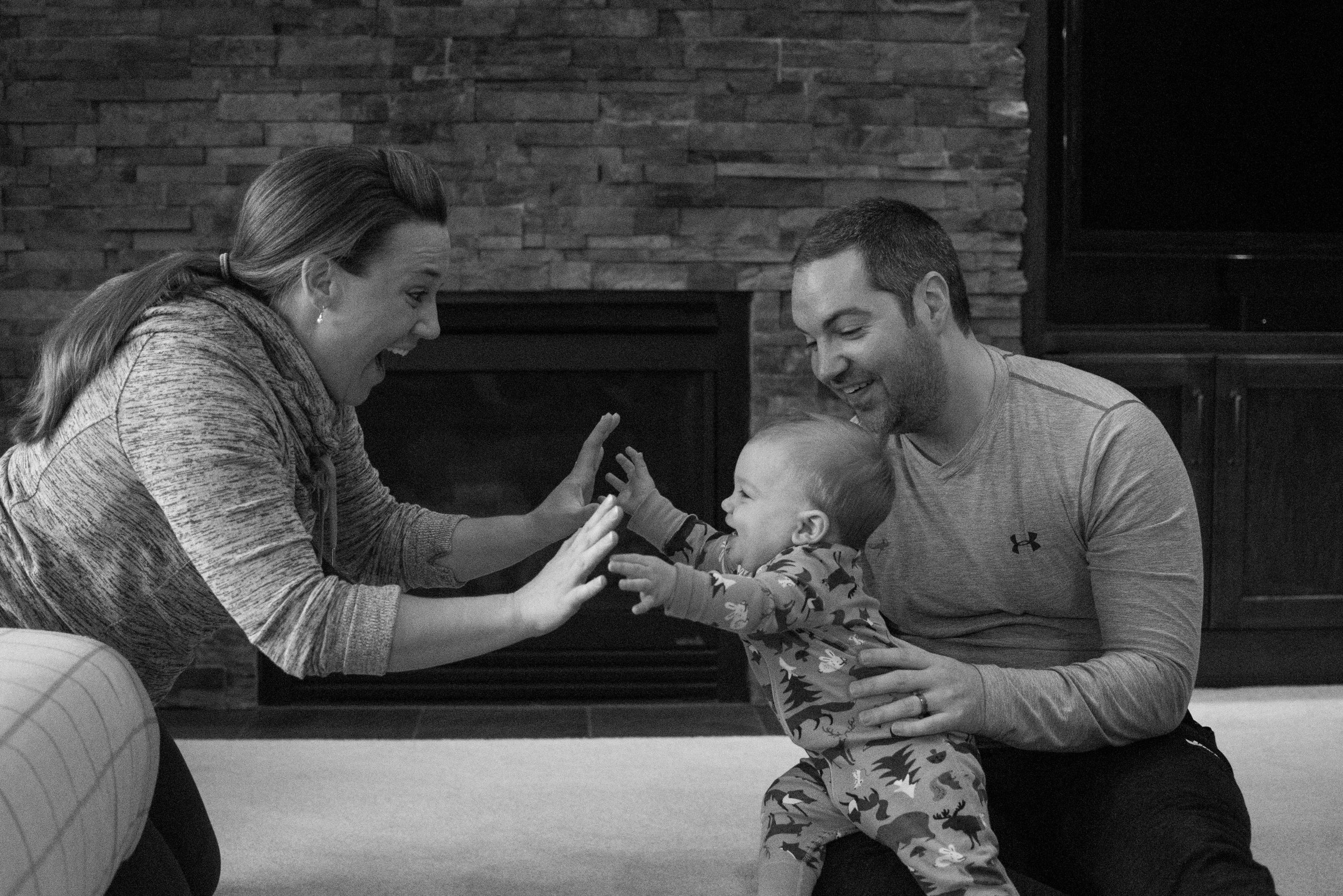 Mom holding out hands to young son, dad holding son on his lap in living room during Appleton Photo Session