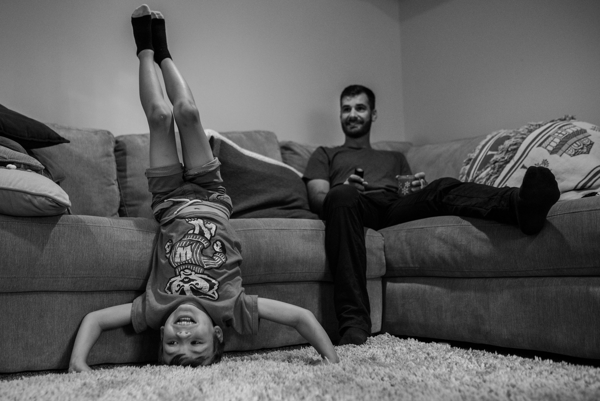Son doing headstand in front of dad on couch during Milwaukee Photography session