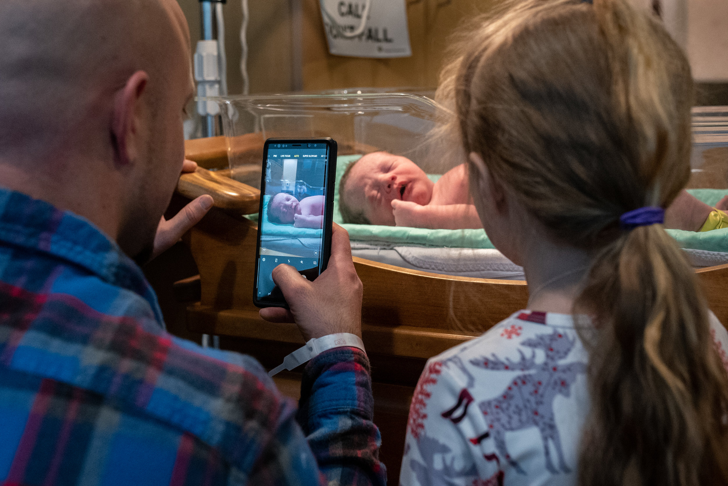 Dad and daughter taking a picture of newborn baby in the hospital.