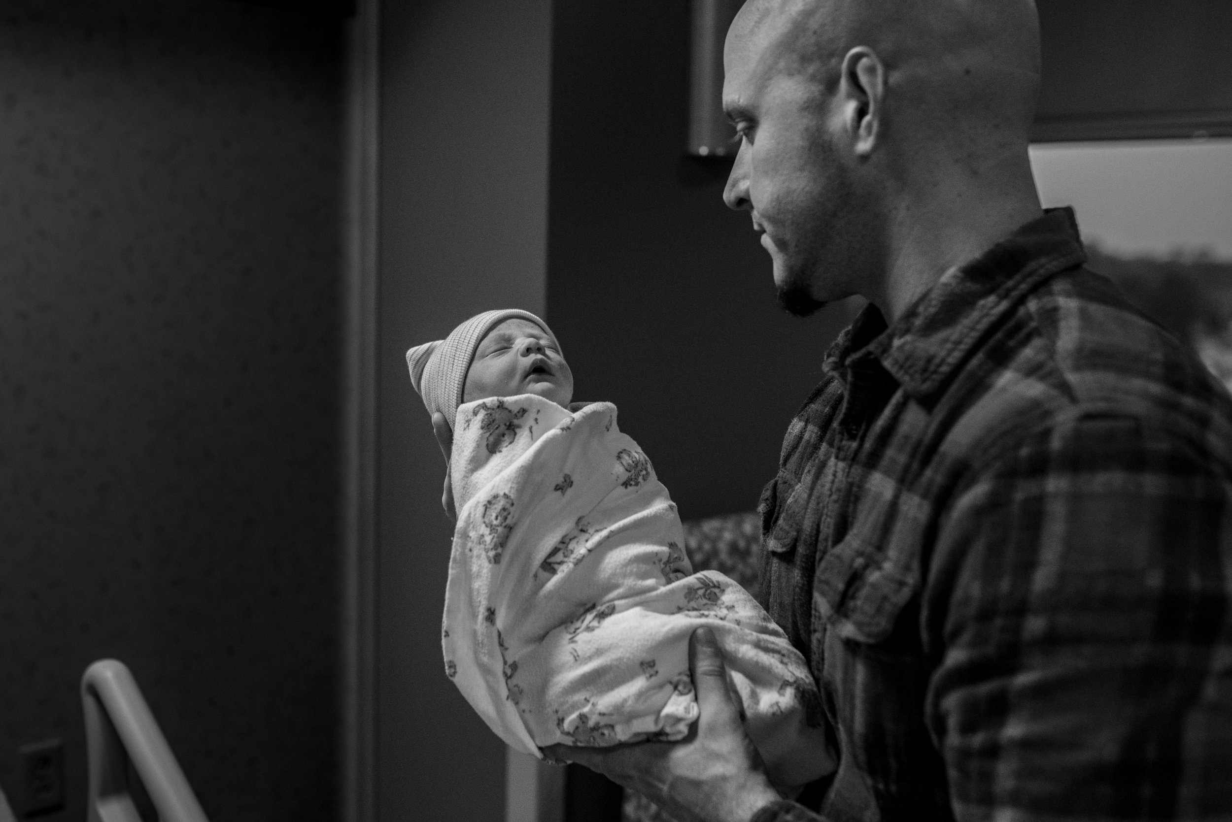 Dad holding newborn baby swaddled in a blanket in the hospital during milwaukee Fresh 48 session