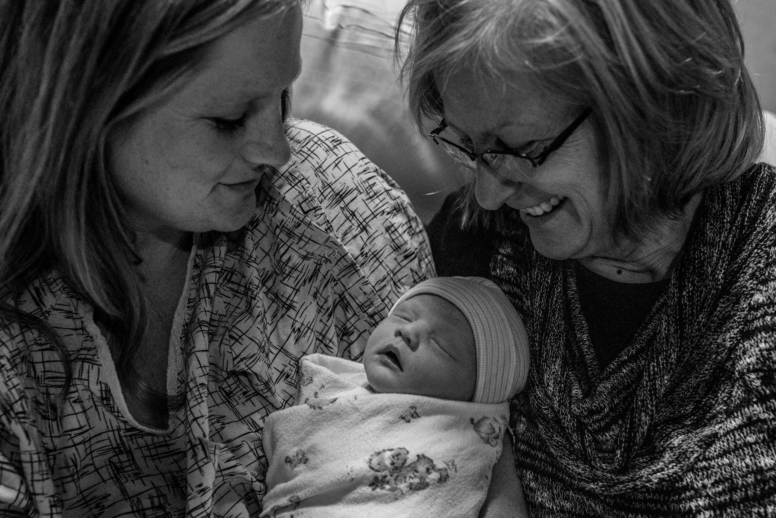 Mom and grandma looking at newborn baby