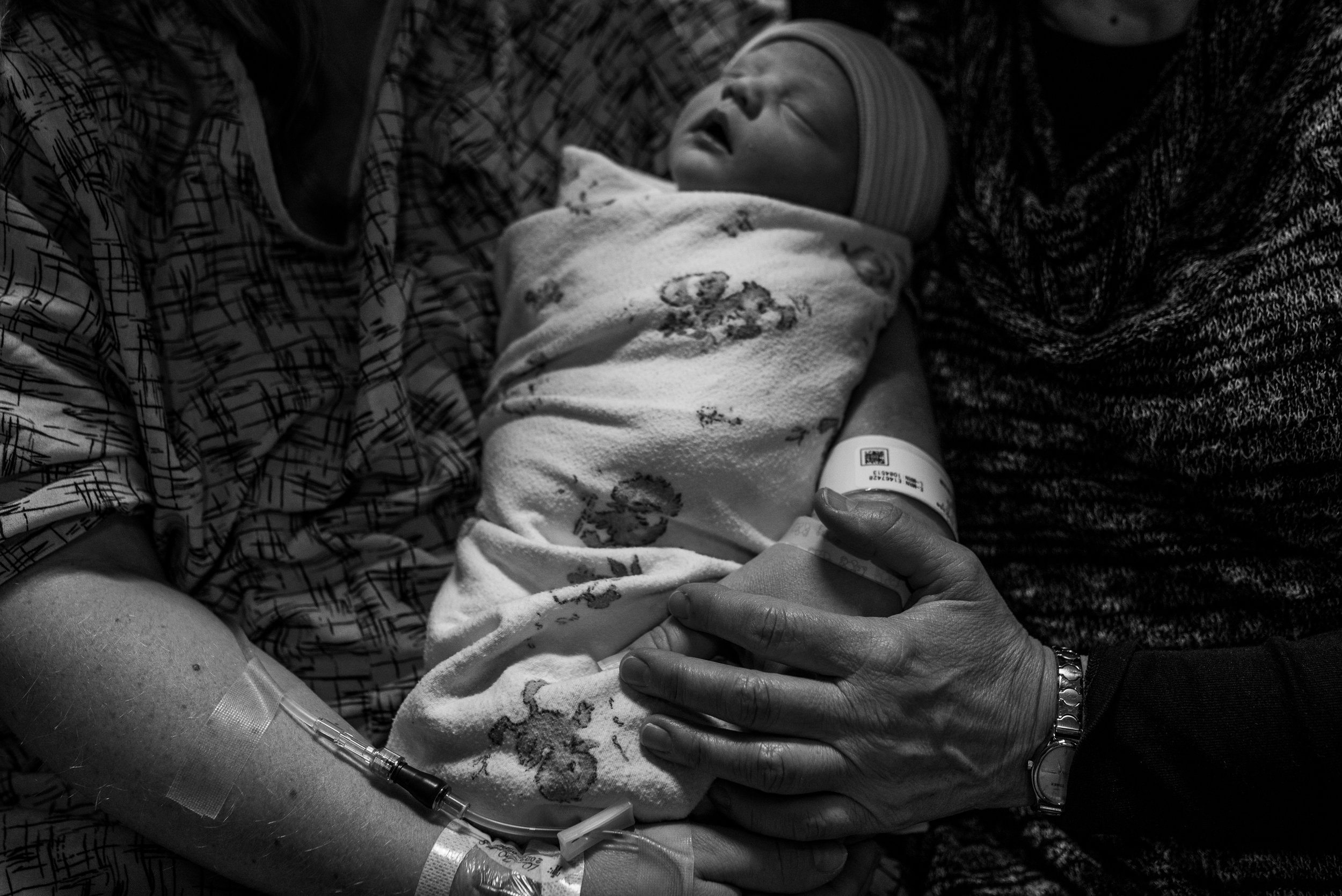 Mom and grandmas hands wrapped around newborn baby in the hospital during Milwaukee Fresh 48 session