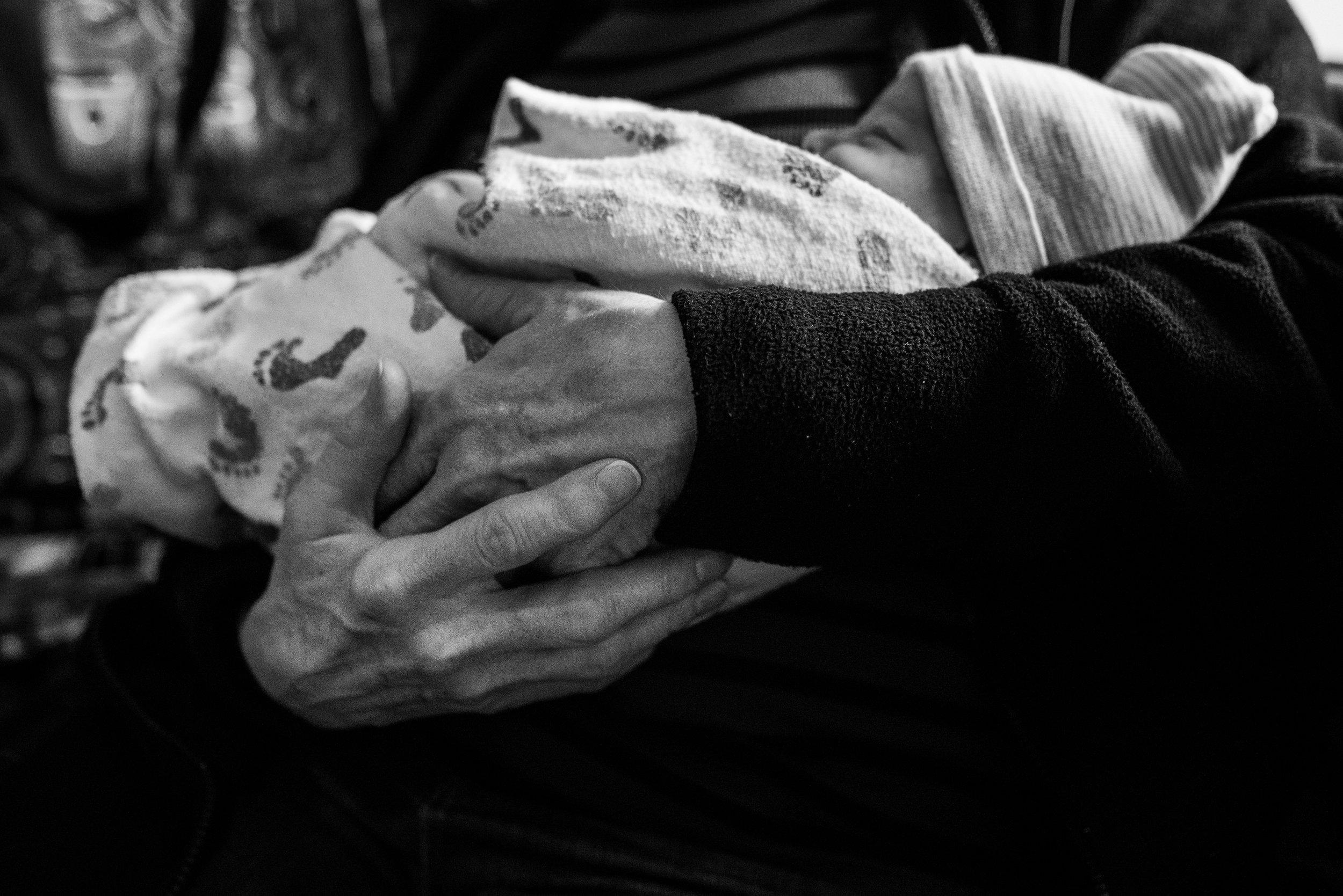 Grandma holding newborn baby in her arms