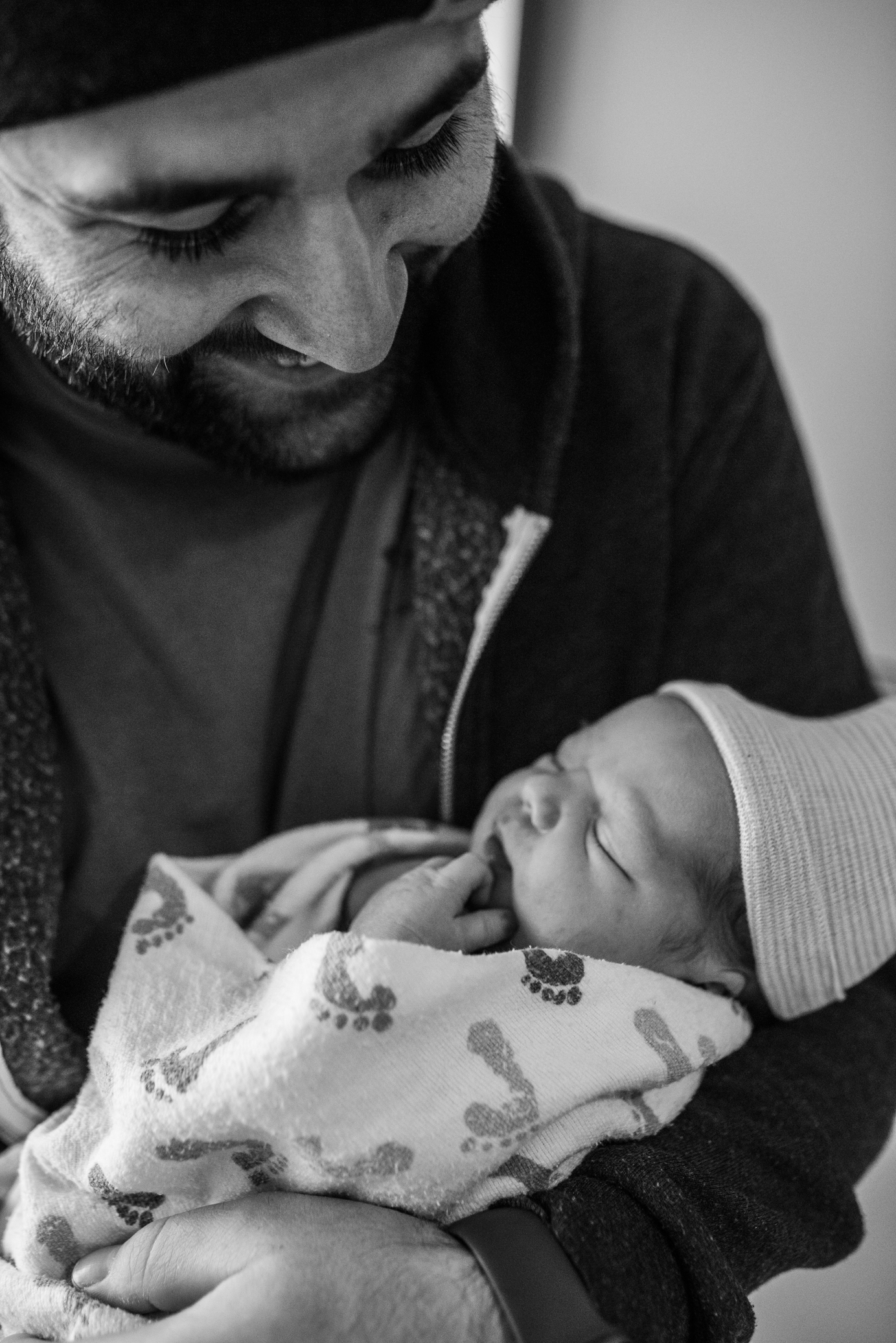 Dad holding newborn baby and smiling down in hospital during Milwaukee newborn Hospital Session