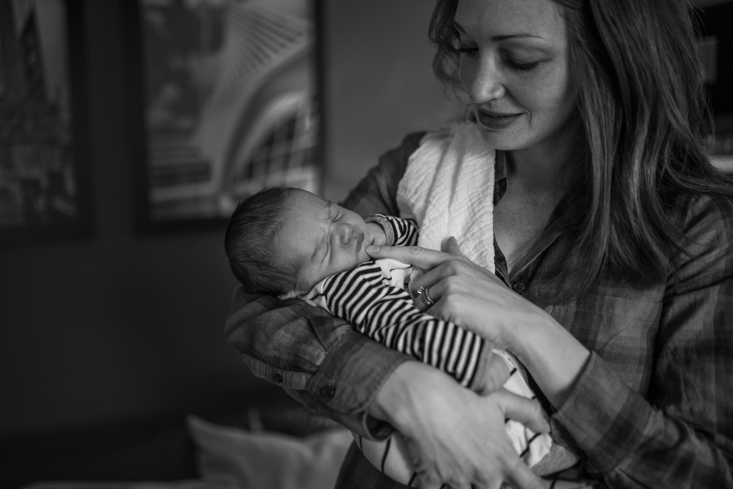 New mom holding newborn baby and looking at baby lovingly poking his chin with her finger