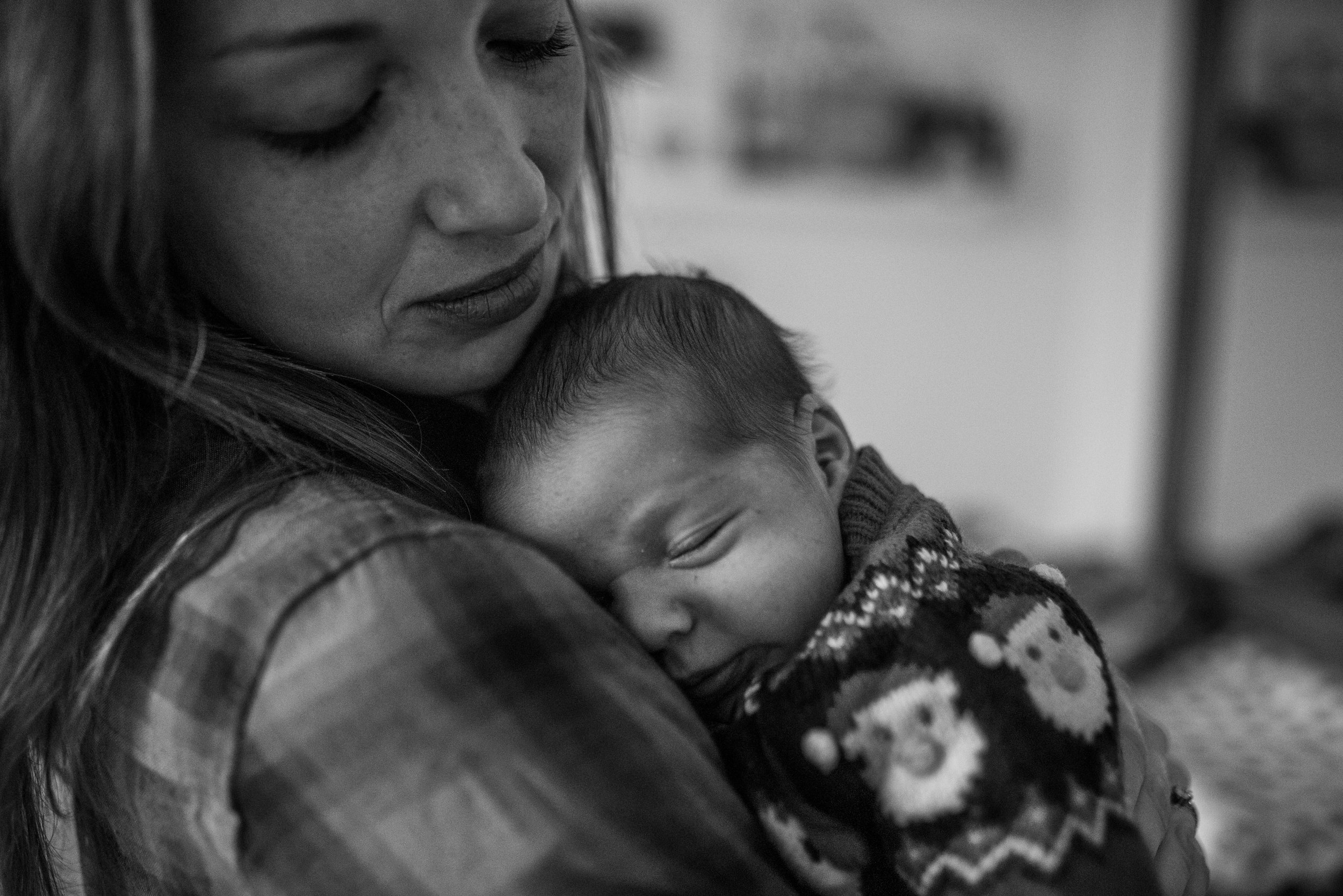 Mom holding newborn baby, both mom and baby have eyes closed