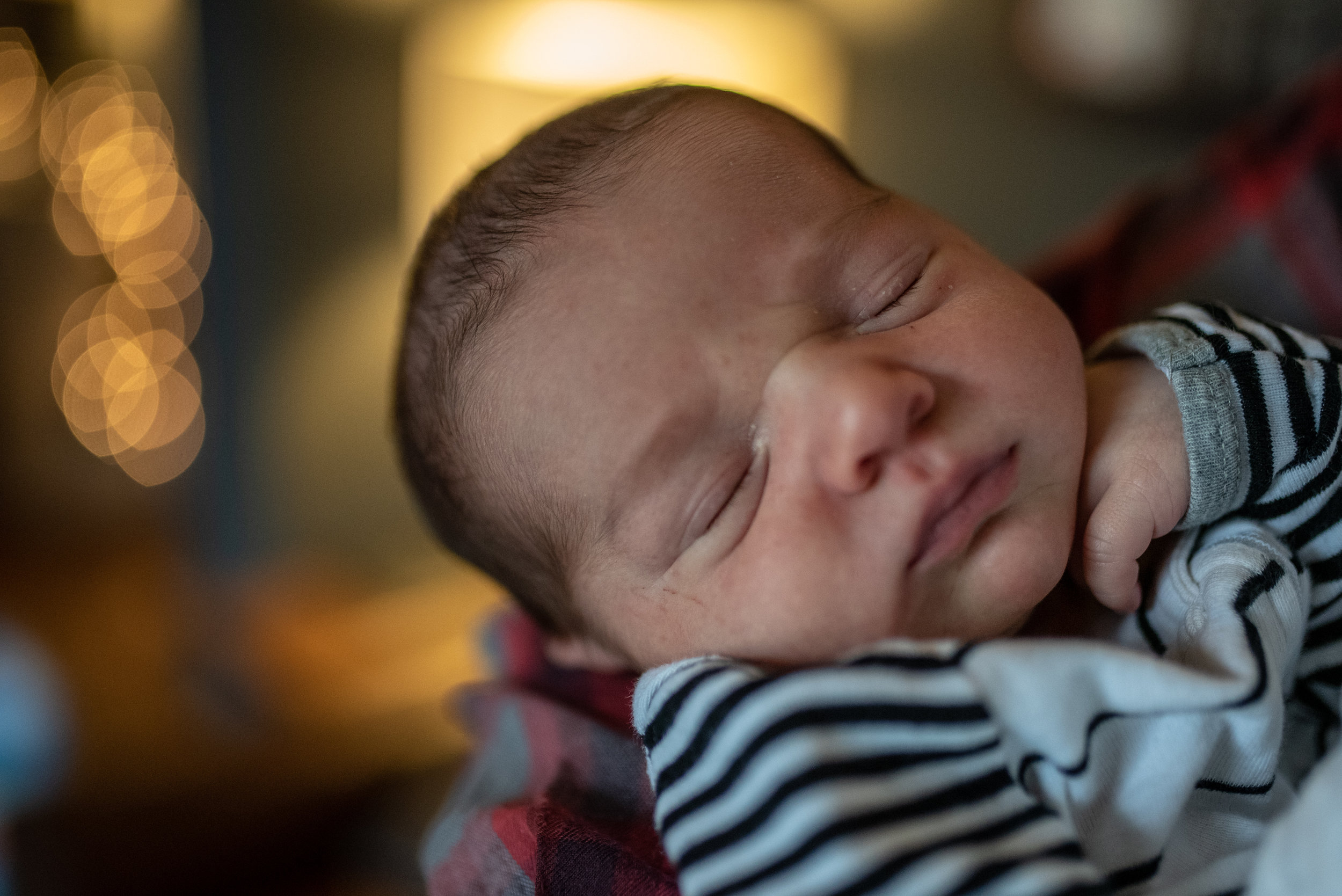 Newborn baby sleeping with twinkling lights in the background
