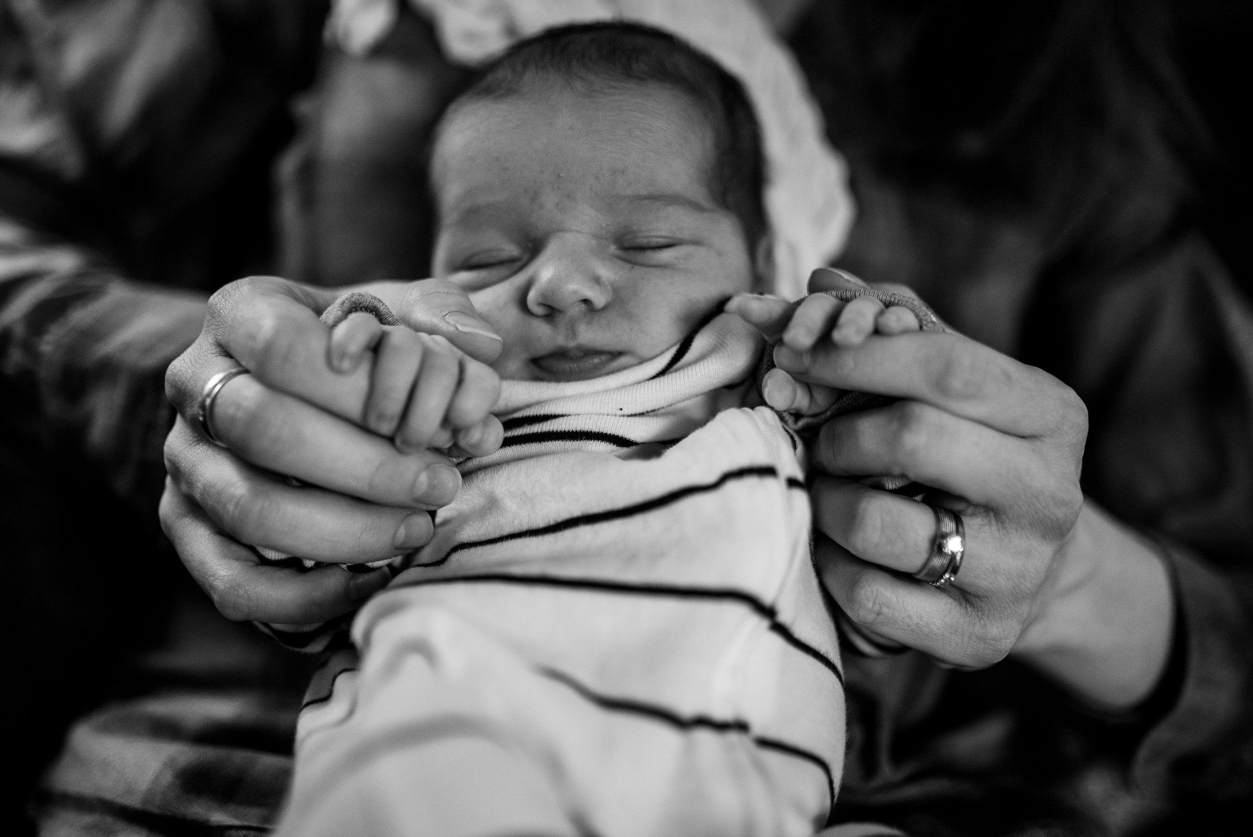 Mom holding newborn babies hands while newborn baby sleeps