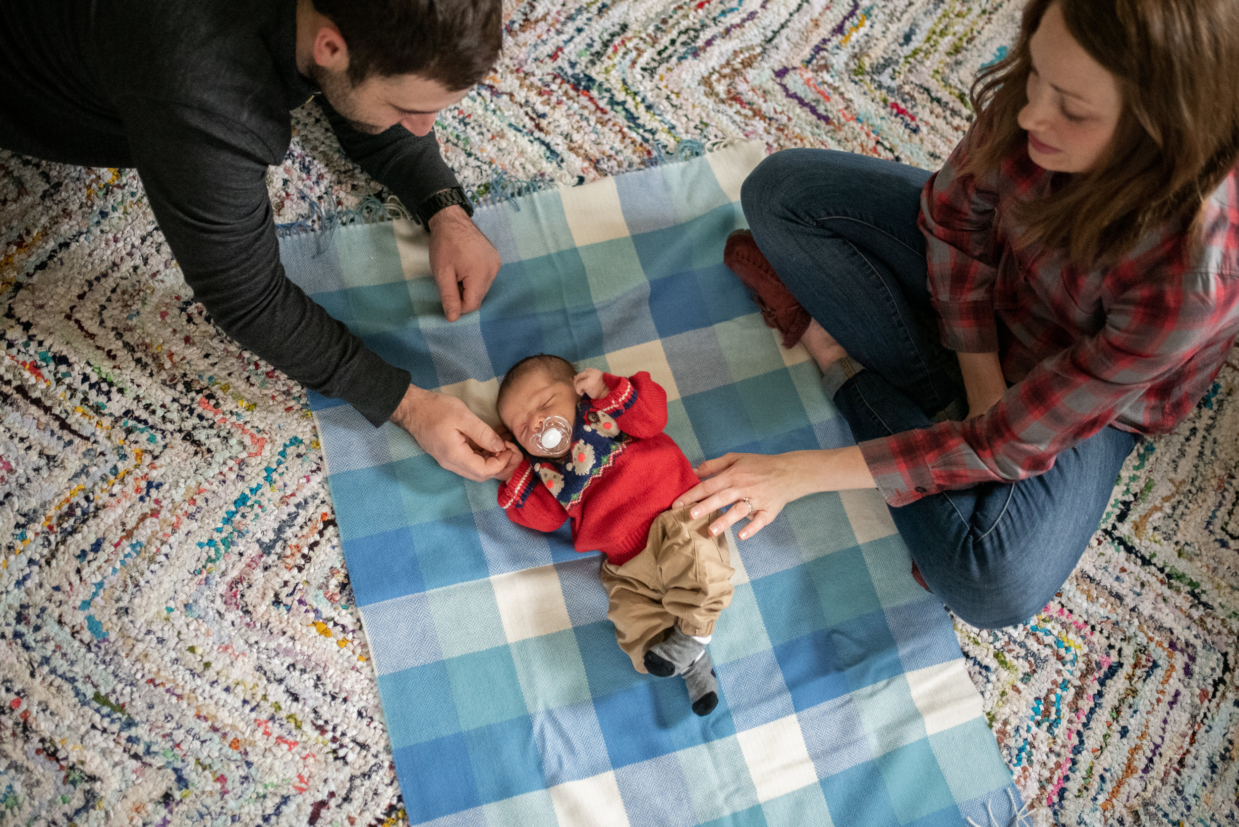 Newborn baby laying on blanket on the floor mom and dad are both gently touching him