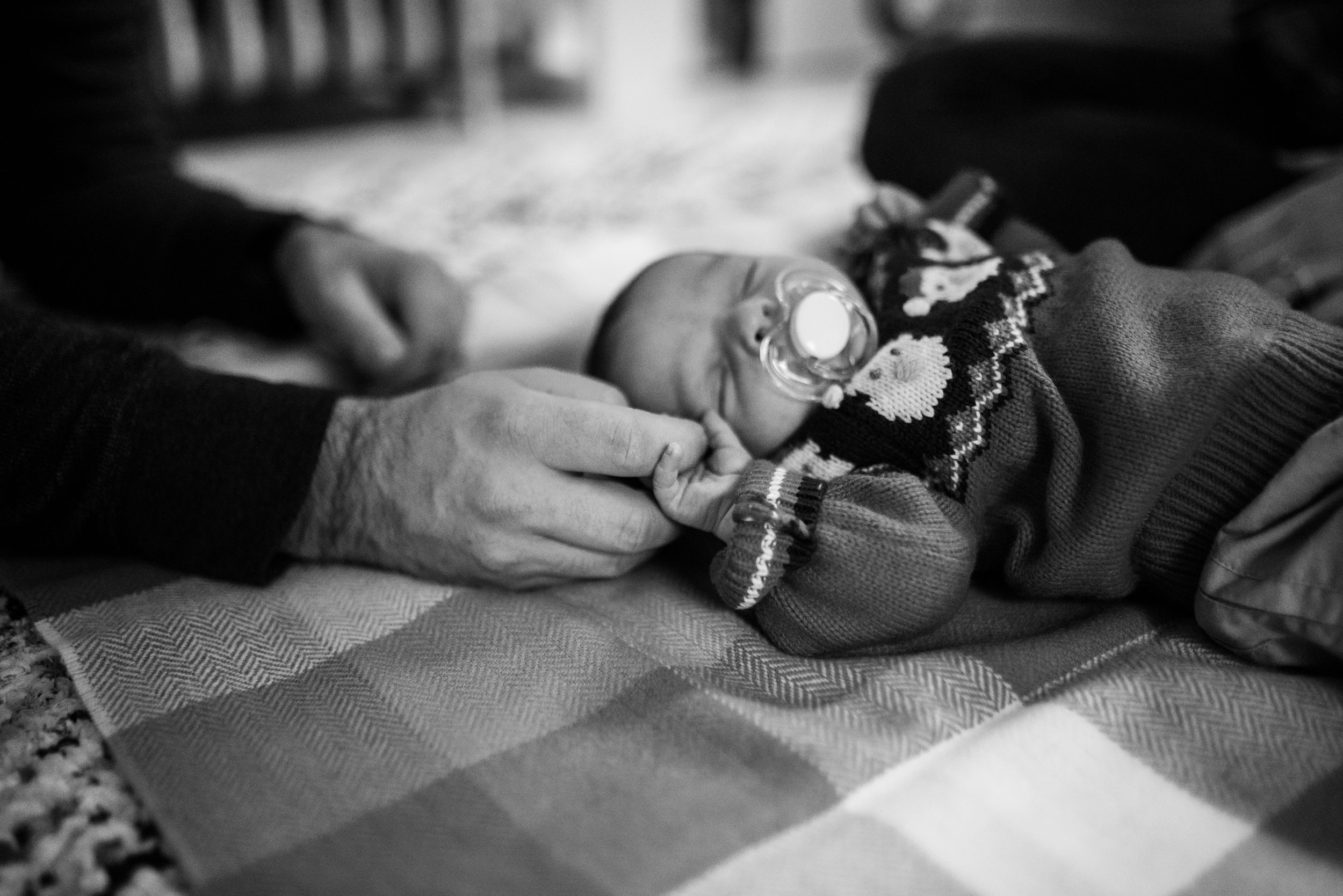 Newborn baby laying on the floor with pacifier in his mouth, holding dads hand