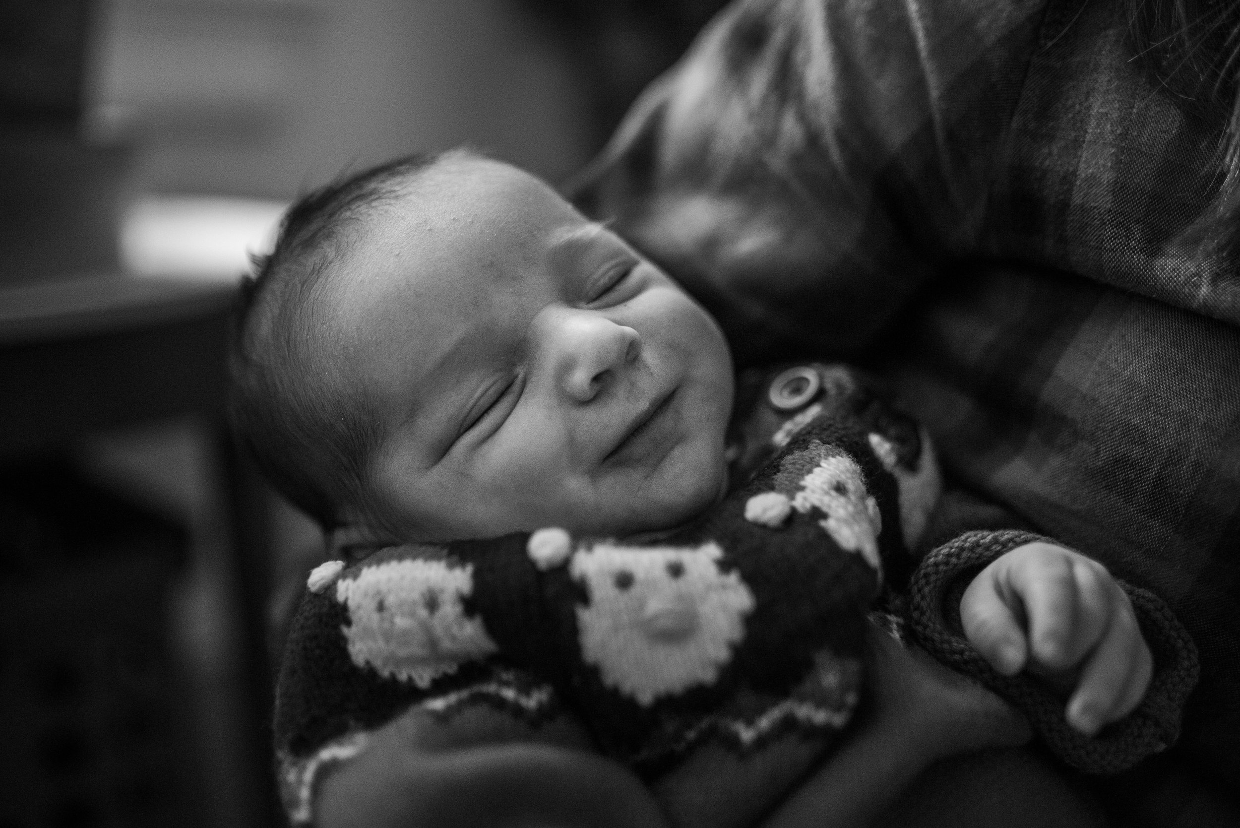 Newborn baby smiling with eyes closed wearing a Santa sweater