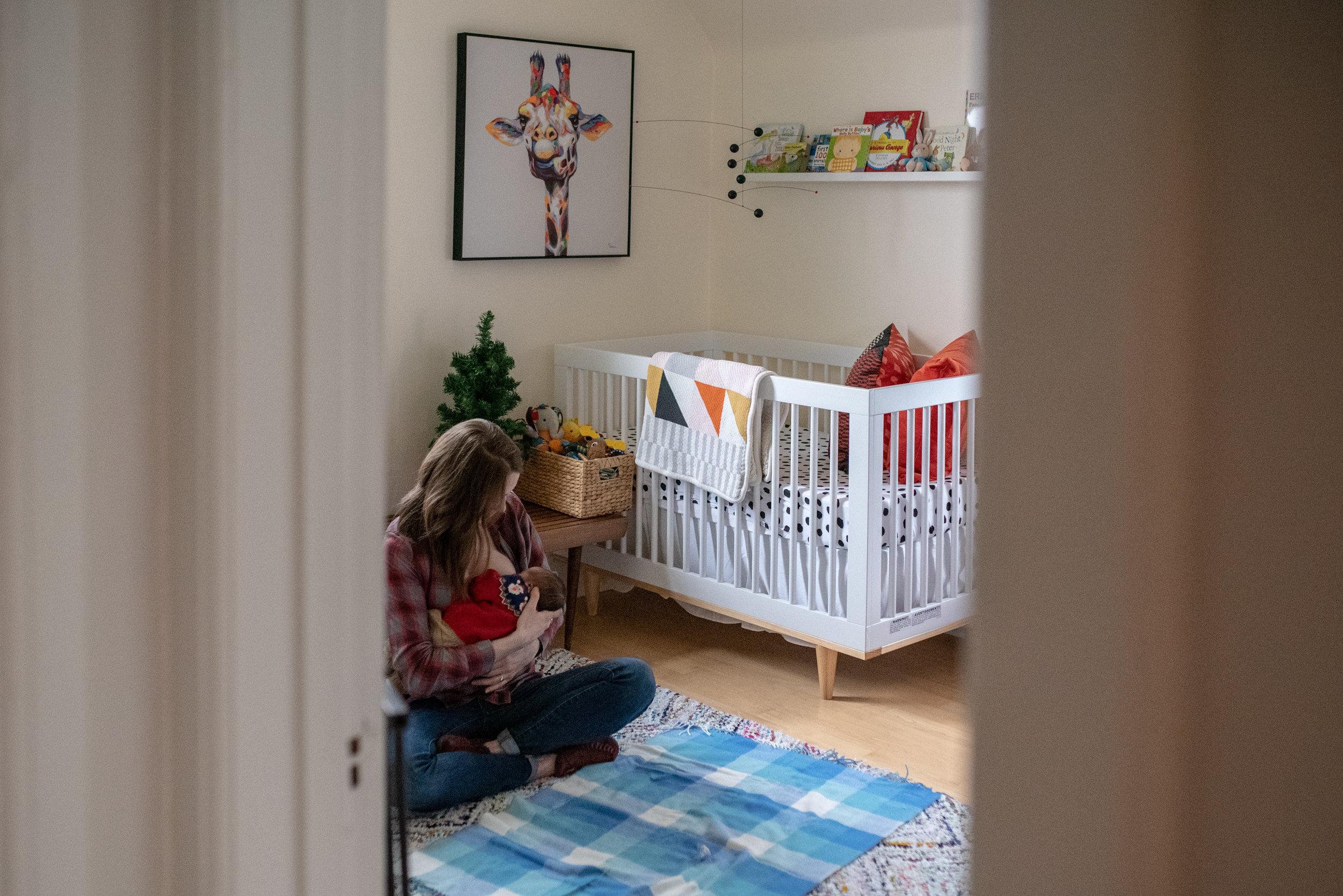 Mother sitting on the floor in babies nursery, breastfeeding baby