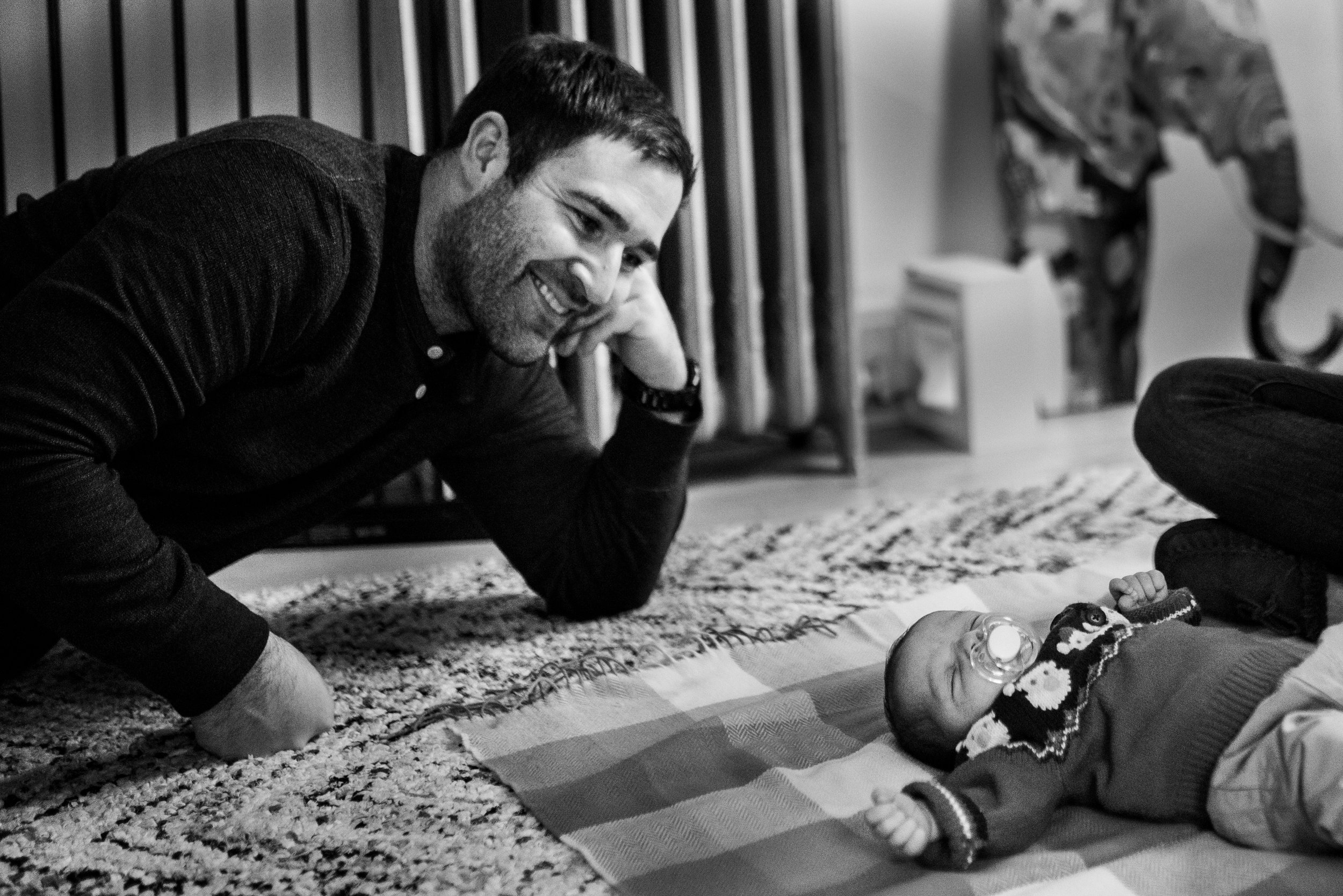Newborn baby sleeping on the floor with pacifier in his mouth, dad looking down and proudly smiling at baby