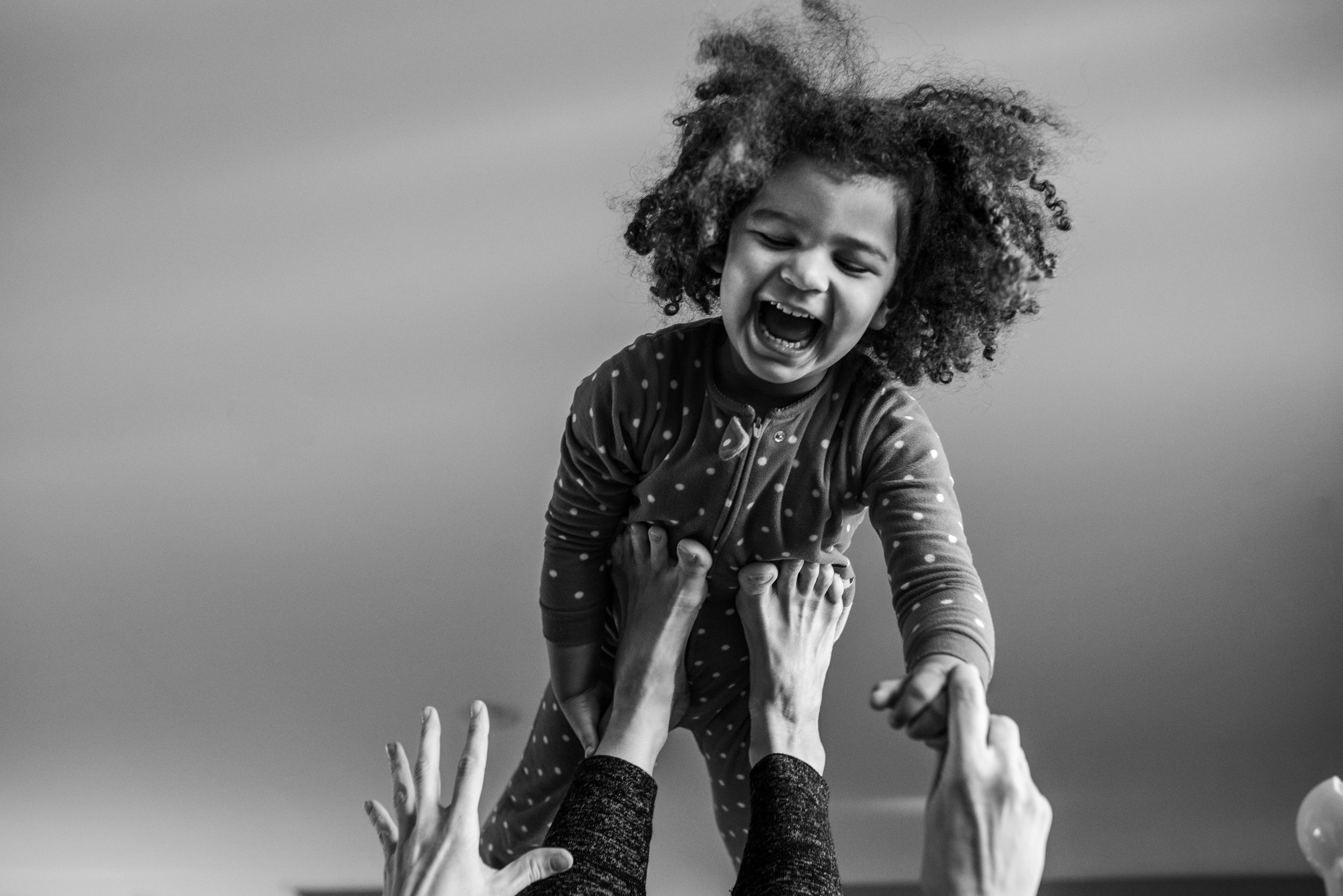 Young girl with curly hair laughing and balancing on moms feet in the air