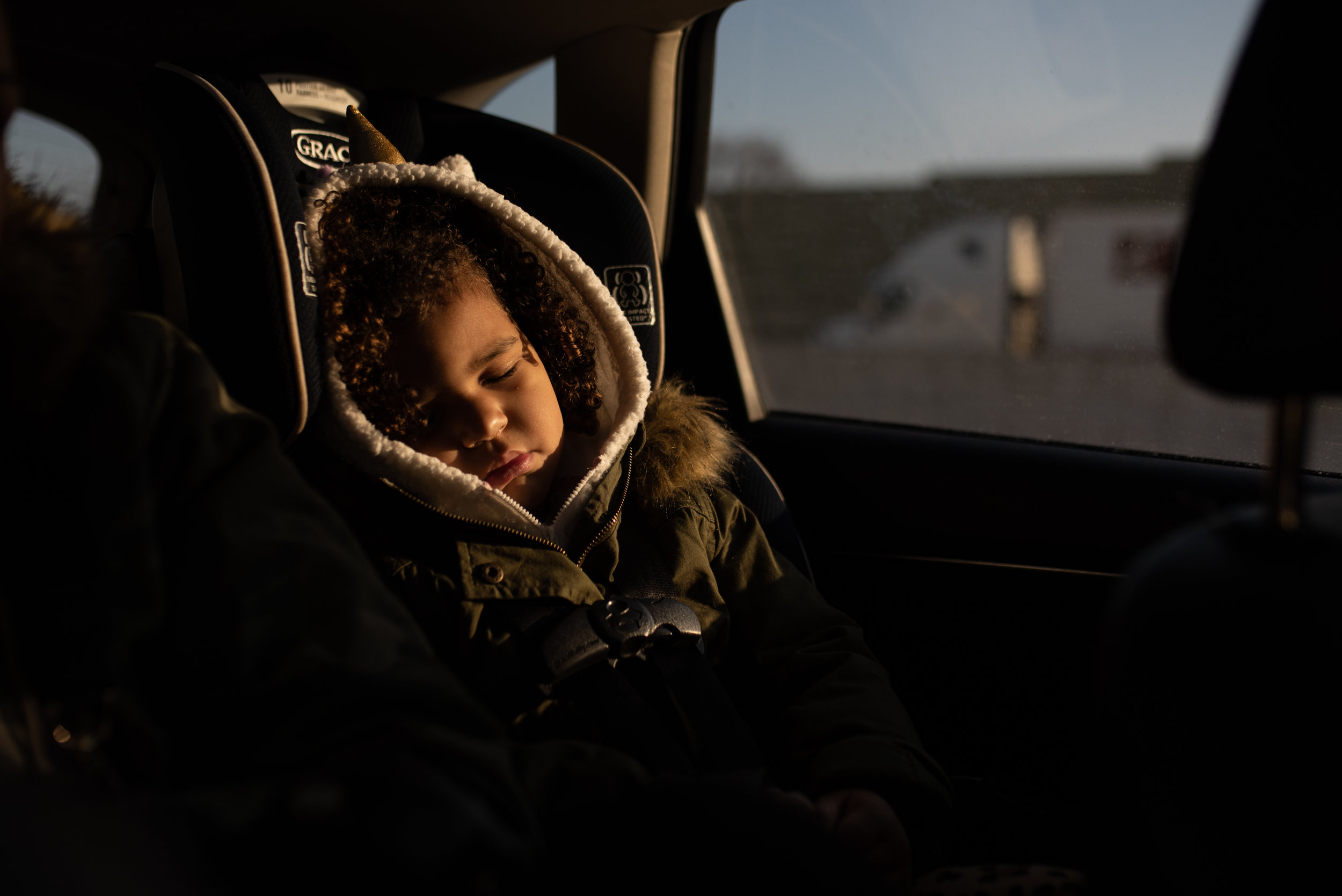 Young girl sleeping in the car, in car seat