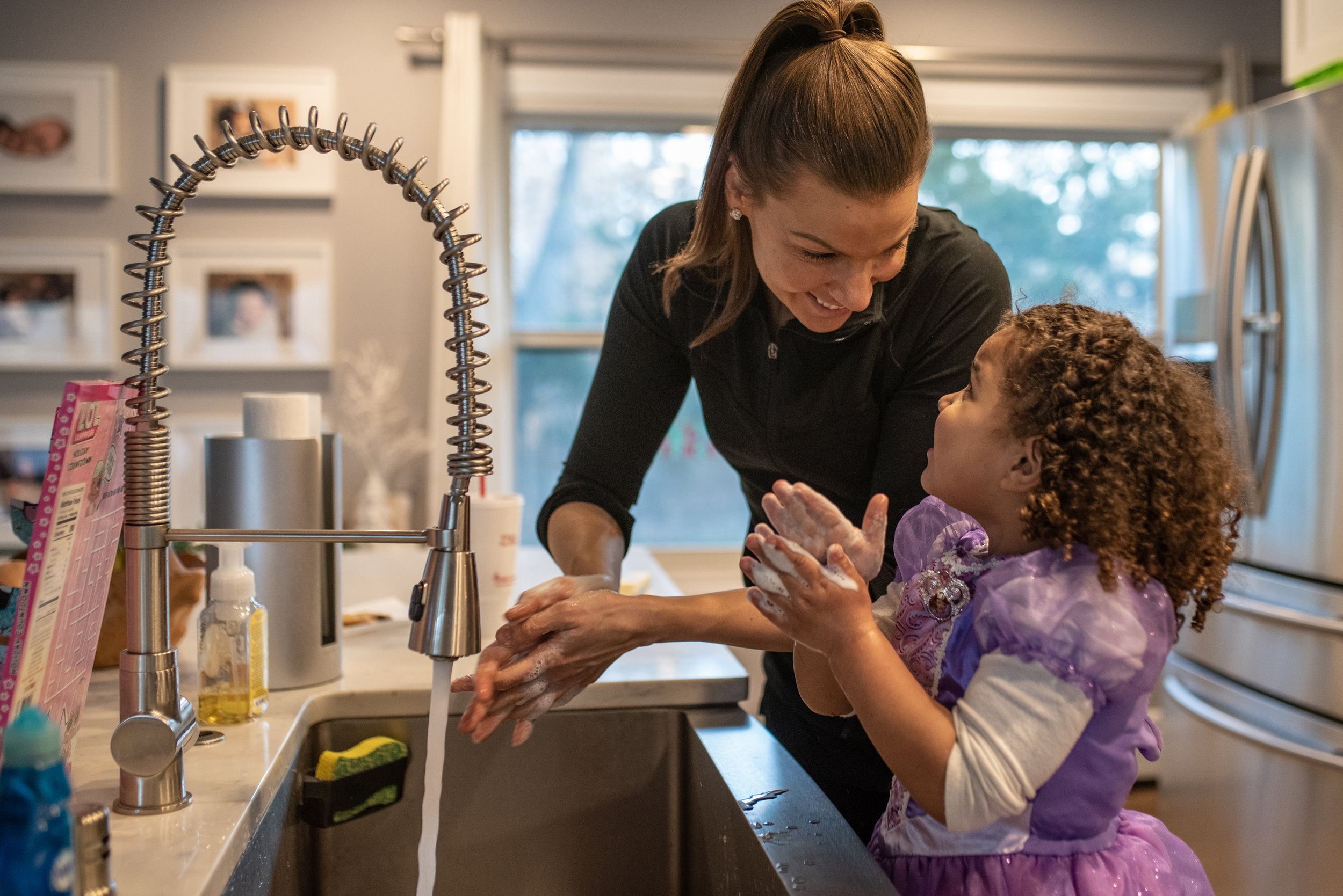 Mom and daughter washing hands in sink and looking at each other