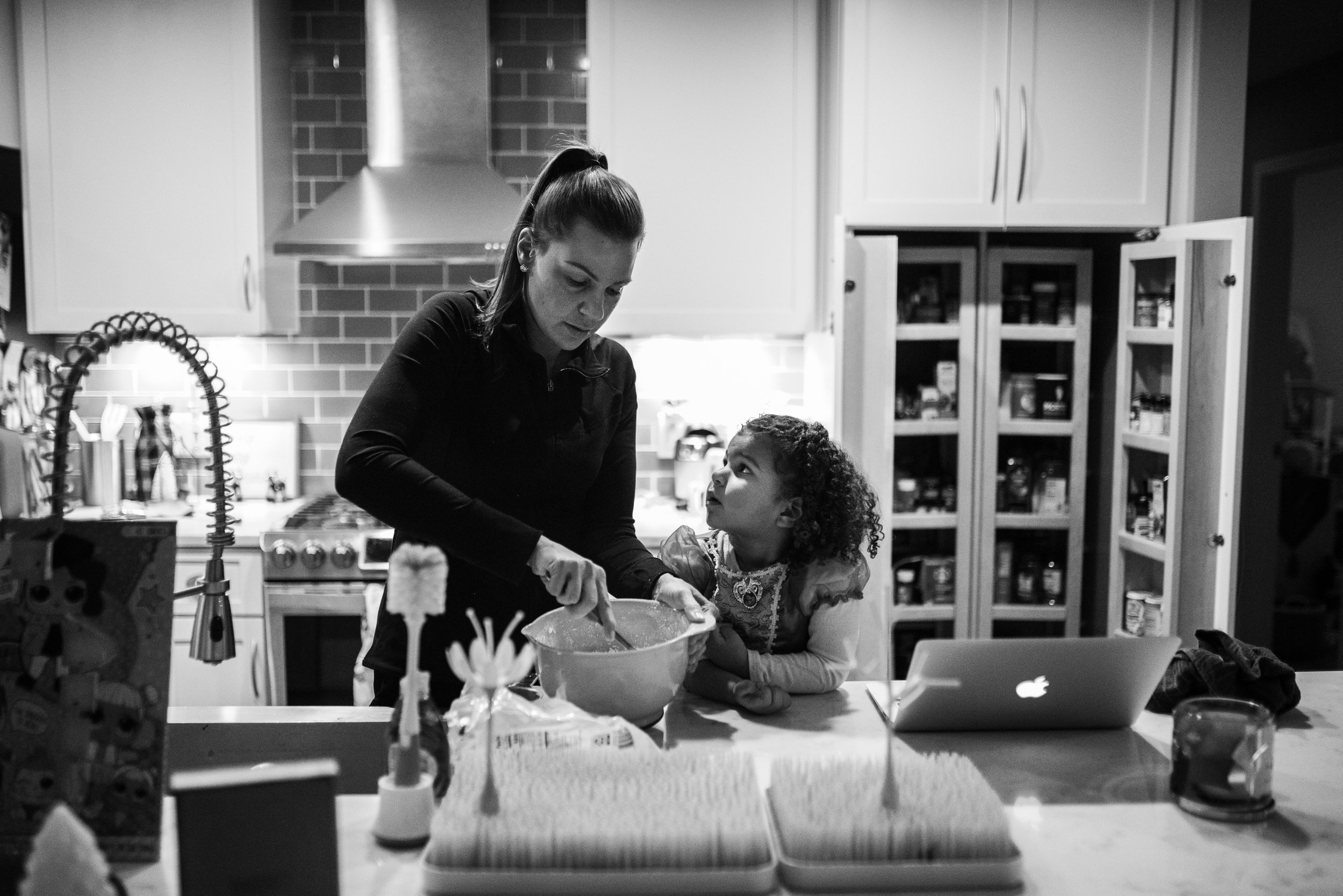 Mom and daughter baking cookies in kitchen