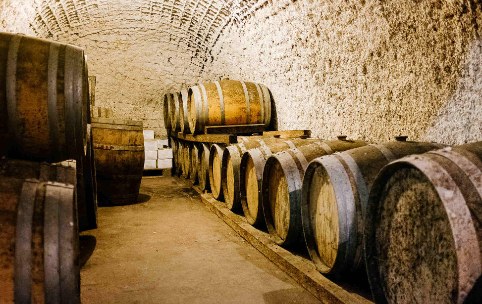 Inside  Hatzidakis winery , the barrels where plenty varieties of Santorini wine are being stored. Source: Hatzidakis Winery