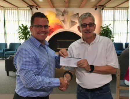 Benicia's Arts & Culture Commissioner Chairman, Terry Scott (right), accepts check from Valero's Paul Adler.