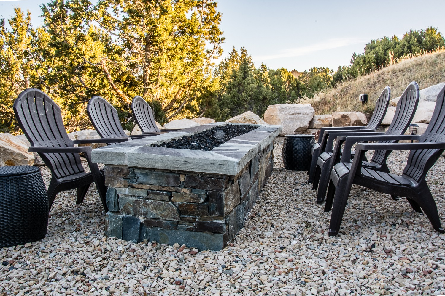 This natural stone fire pit brings uncompromising beauty you can't find with concrete pavers or artificial cultured stone. Notice how the natural boulders, crushed rock, and veneer blend in with the surrounding area.
