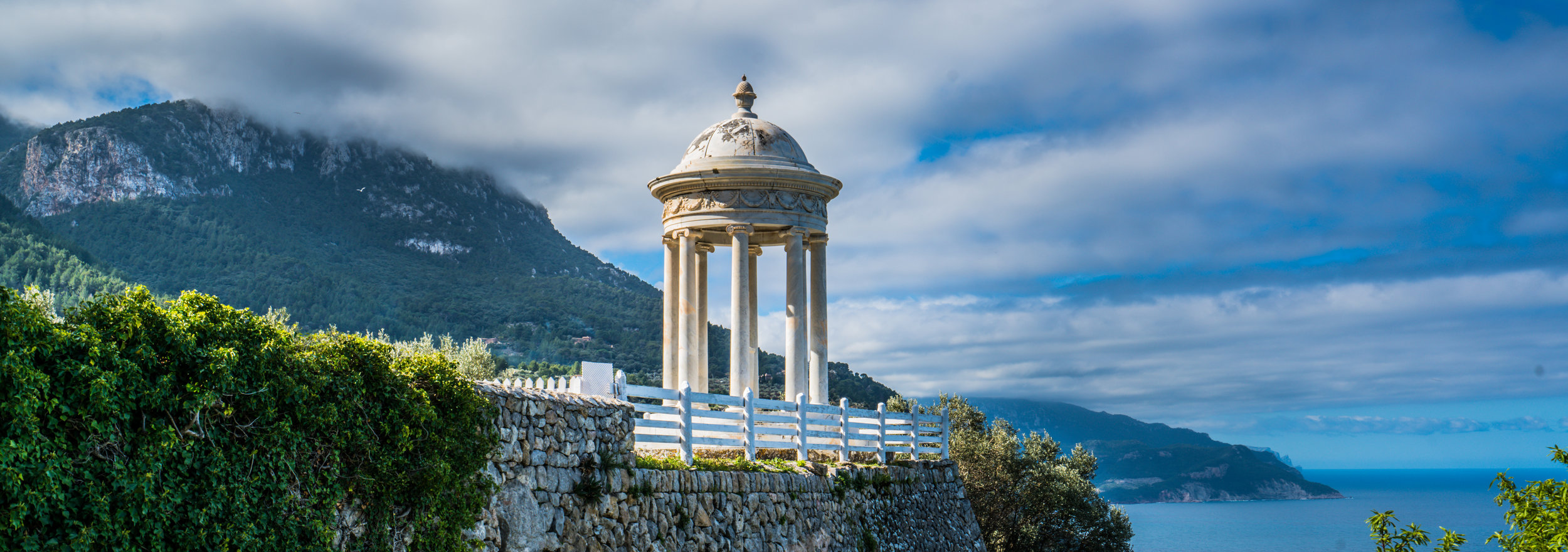 Idyllic white temple on top of the sea surrounded by olive orchard  DBPhotography