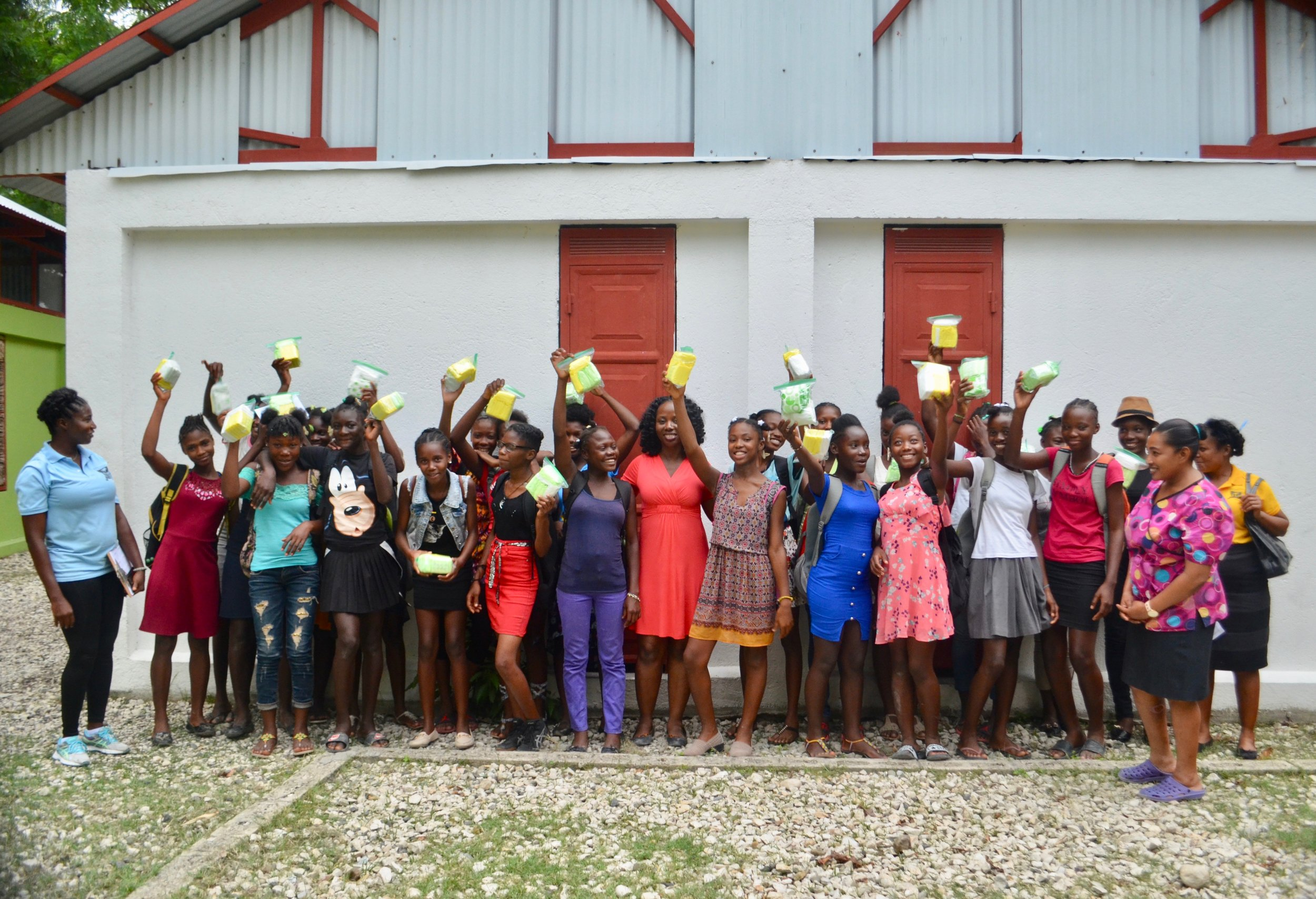 The female students of L'Ecole de Choix in Haiti holding up pads distributed by Cycle Forward.