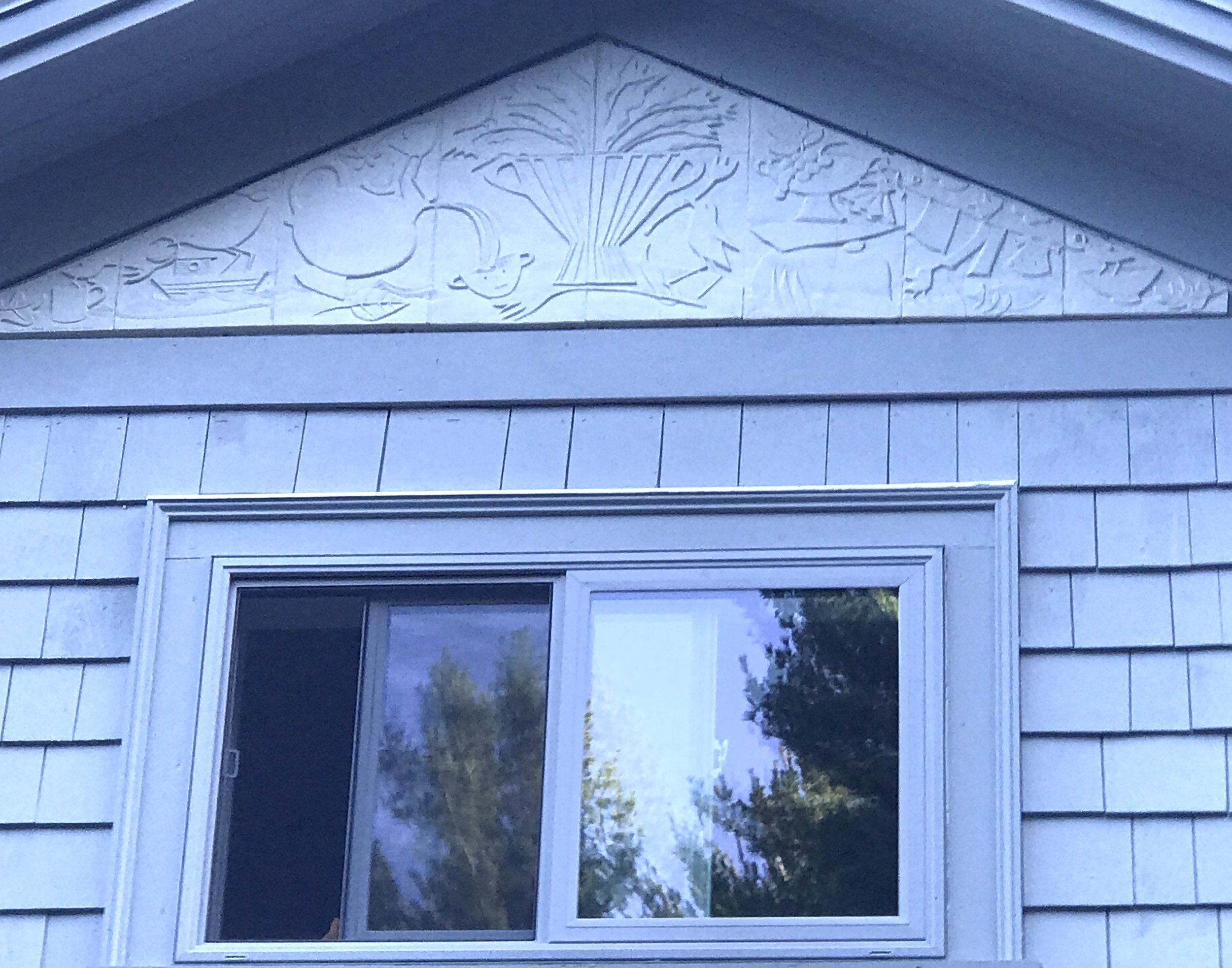 This is an early morning photo of a new porcelain pediment that was just installed yesterday on our new addition. The piece is carved porcelain, @ 7 ft at the base. Decorative and functional wood trim will be applied to the border shortly. We thought about all types of finishes for the piece such as multi-colored images to Wedgwood figure/ground solutions and settled on simple bas-relief. One nice thing about the piece is how it is very subtle. It is on the second floor, pretty high up. It is integrated nicely with the house without calling too much attention to itself.  The imagery comes from Francine's work: the laundry line, boat, flowers, ceramics, piled rocks and, of course, busy birds.  The piece will look different in every season. I think it will be most dramatic when the sun is lower (winter) and in fall and spring. With the sun being so high in the summer, a lot of shadow falls over the piece from the generous overhang.  We will post other pictures at different times of year to see if this is true. It was enormously fun to do. We will see how it lasts through our weather.