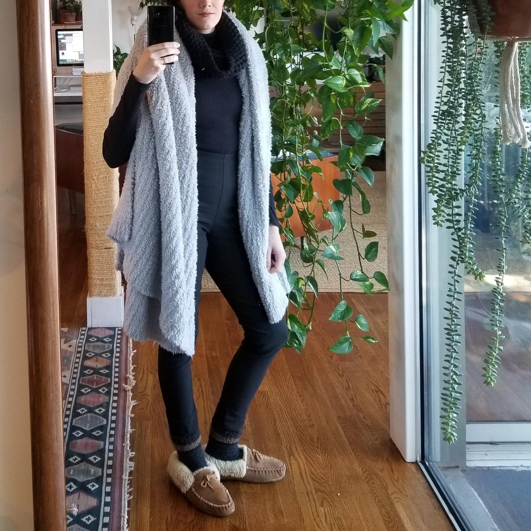 Resplendent in blanket, she works from home. -