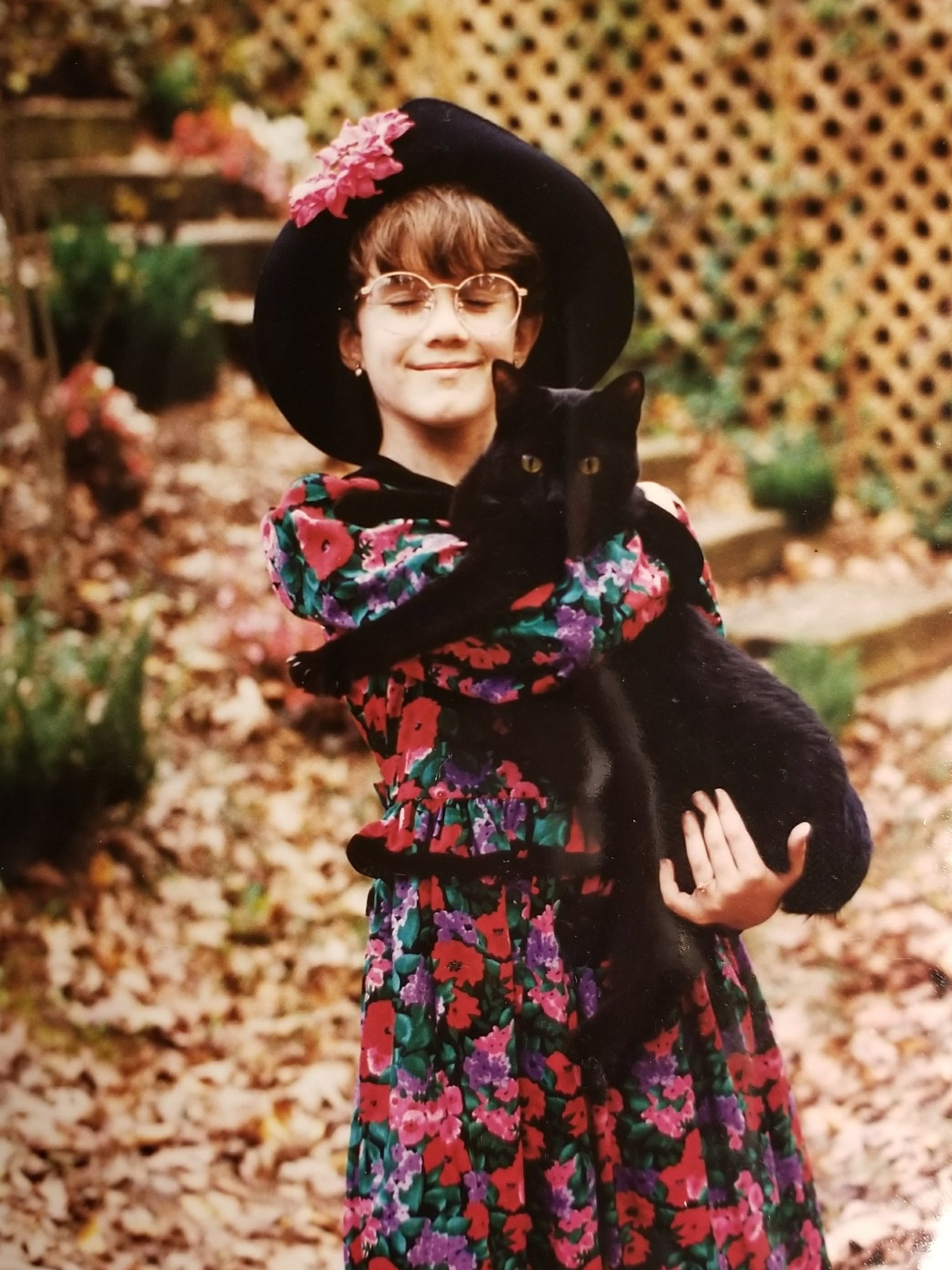 Purrfect accessory - The pink flower on the hat really makes a statement on top of the wild floral pattern of the dress. But what keeps it all coherent is the black trim!Accessorize with your favorite black cat to bring it to the next level.