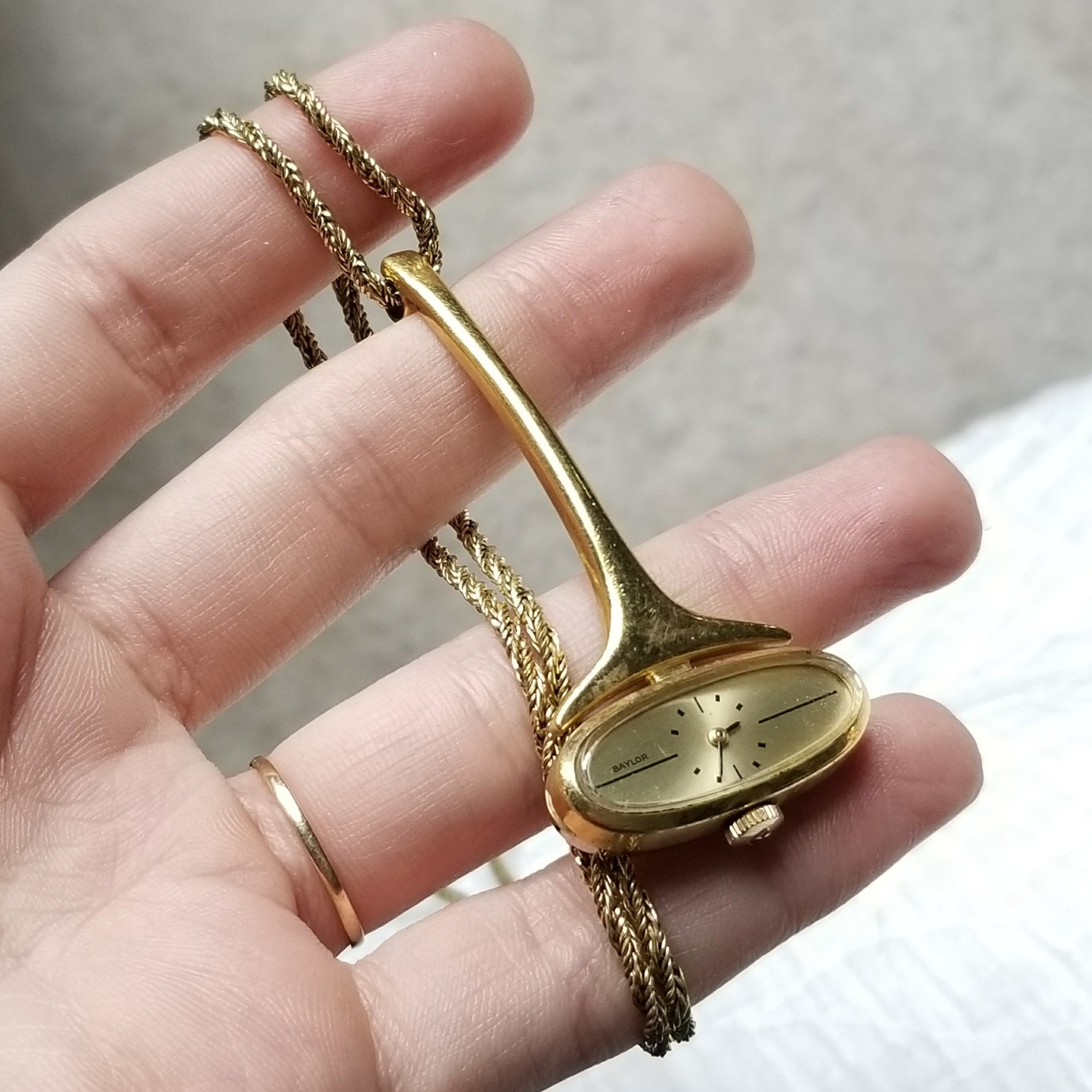 The gold necklace watch.