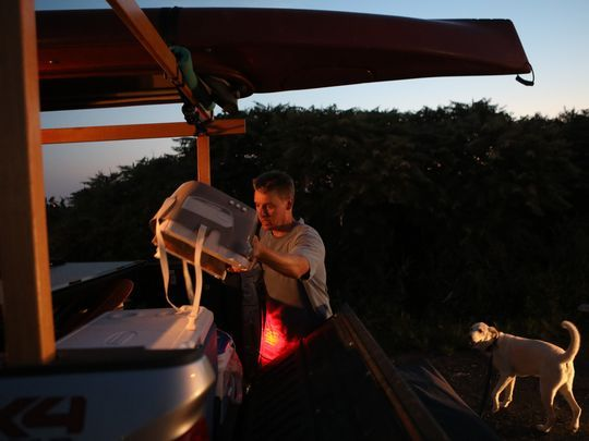 Brett Roper of Vienna, Virginia, rearranges items in his truck during a stop at The Vince on his way home from a two-week trip to Maine with his dog, Woody.  Photo: Kevin R. Wexler/NorthJersey.com