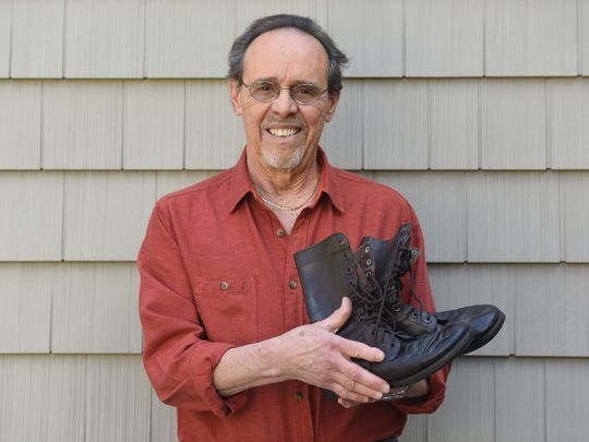 Paul Caminiti holds the pair of Army boots he was wearing when he and his fellow recruits pulled survivors and bodies from the wreckage. Photo: Viorel Florescu/NorthJersey.com