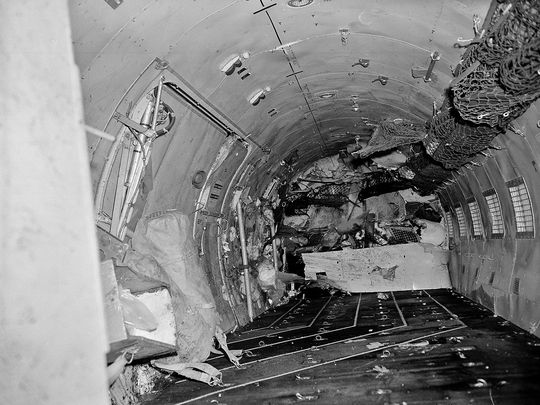 An investigating soldier, far end center, looks up through the window into the cabin of the plane.Virtually every seat in the cabin was ripped loose during the crash. Photo: associated press