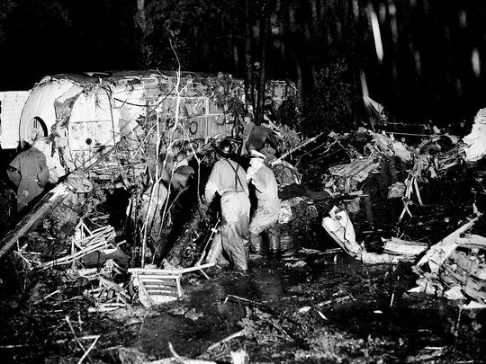 Firefighters and military personnel, standing calf-deep in water, search the wreckage.  Photo: AP
