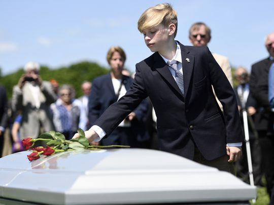 Tyler Ryan, 13, places a rose on his grandfather's casket.  Photo: Danielle Parhizkaran/Northjersey.com