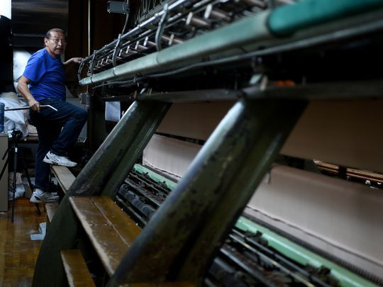 Edgar Acosta of Clifton climbs up and down the looms all day. He has worked at Deerbrook Fabrics for 37 years. Photo: Amy Newman/NorthJersey.com