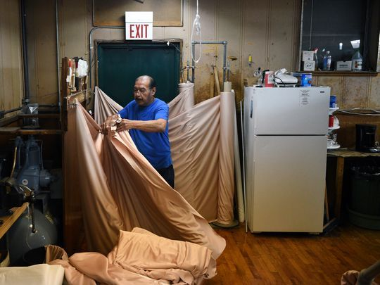 Edgar Acosta folds and cuts fabric before putting it on one of two Saurer looms, which were built in 1955.  Photo: Amy Newman/NorthJersey.com