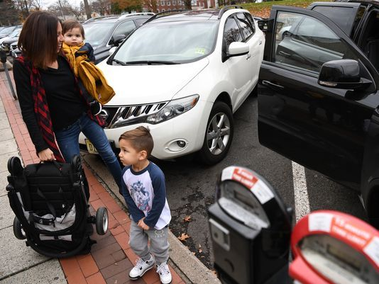 Danielle Gutierrez loads her children into her vehicle on Saturday. She was parked in a metered 15-minute parking spot in downtown Ridgewood.  Photo: Michael Karas/Staff photographer