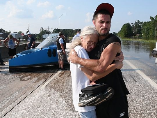 Amy Torres hugs her brother Cody Adams, of Beaumont, Texas, after he was rescued from being stranded on a median in the middle of State Route 96 in rough flood waters in Beaumont on Sept. 2, 2017. Adams was saved by Bill Zang (not pictured) in his hovercraft.(Photo: Danielle Parhizkaran, Northjersey.com via USA TODAY NETWORK)