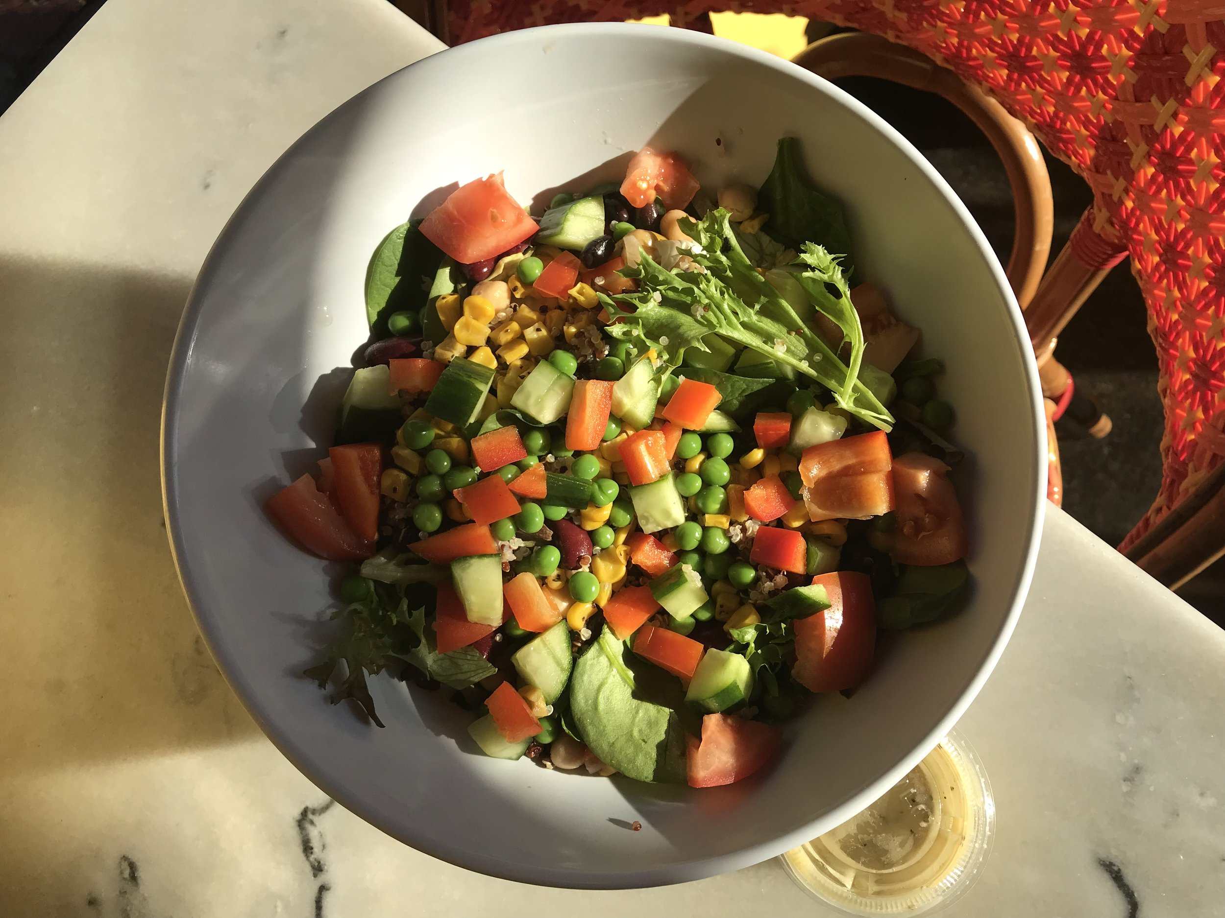 Veggie Protein Salad - Garbanzos, kidney beans, black beans, quinoa, roasted corn, peas, cucumber, and red pepper, on a bed of greens, served with lemon vinaigrette.