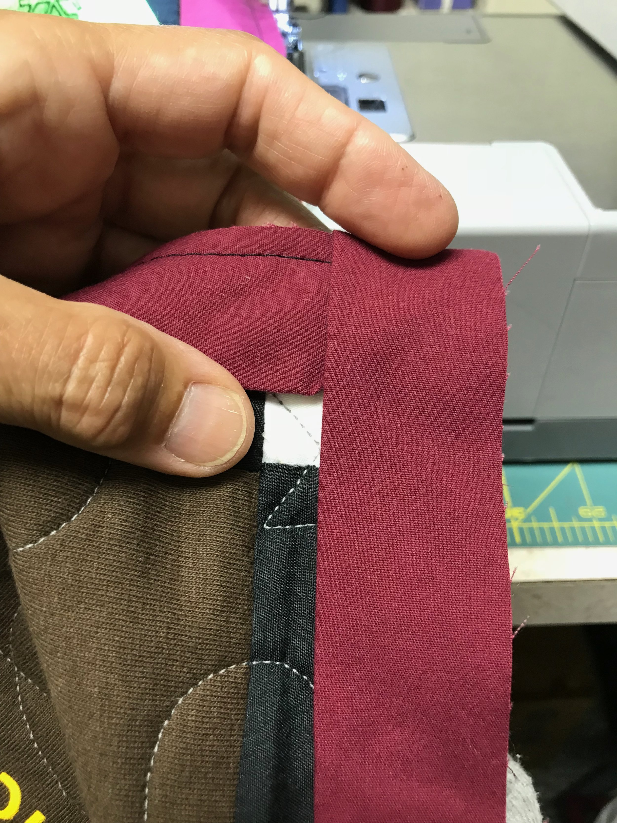Fold the binding down so it aligns with the top and side edge