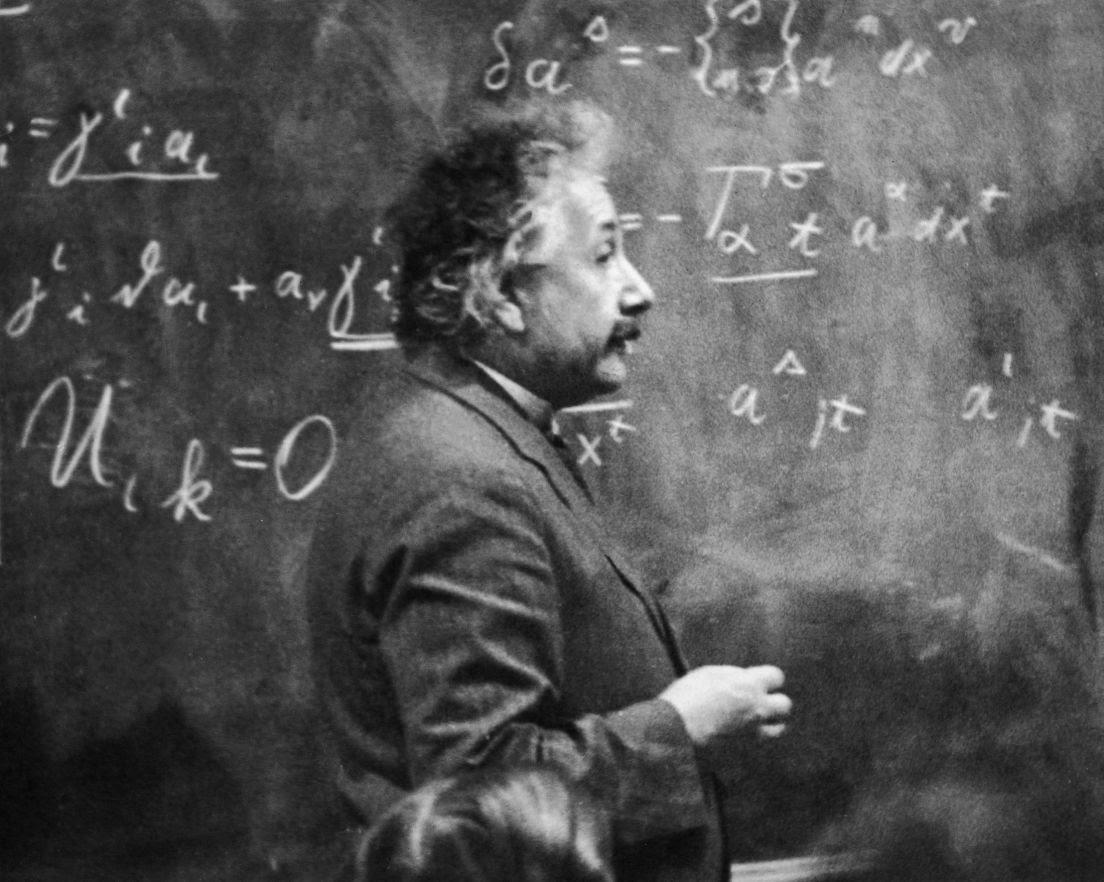 El físico Albert Einstein (1879 - 1955) de pie junto a una pizarra con cálculos matemáticos escritos con tiza. Hulton Archive, Getty Images