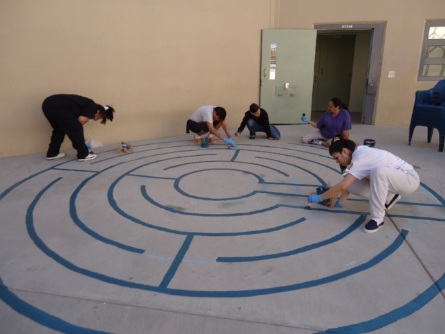 Incarcerated women and staff at the Santa Fe County Adult Detention Facility creating the first labyrinth in the rec yard, 2013.