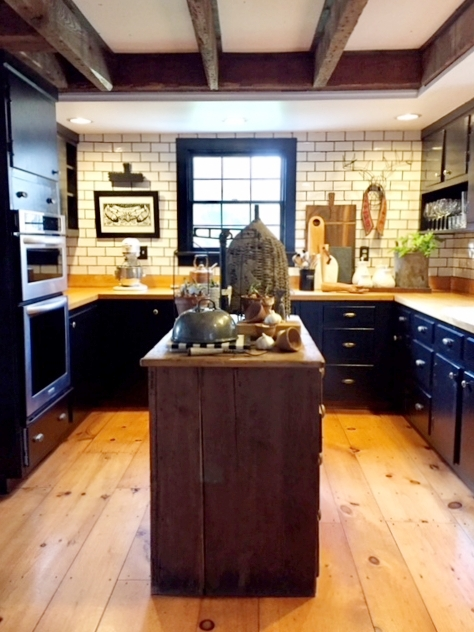 We wanted a certain feel in the kitchen--a bit of a nod to a service kitchen. The hand-made subway tile from  Klaffs  helped to achieve that look. We coated the cabinets with black paint, replaced the hardware with antique knobs and  handles, added a farmhouse sink, and updated the appliances.