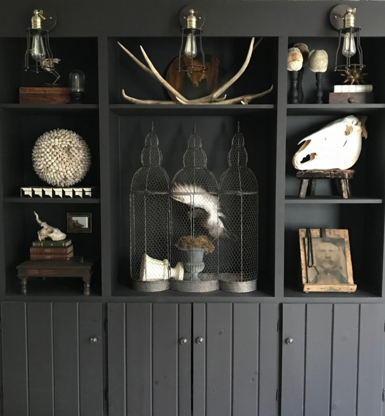Artfully and Functionally Curated - Inspired by curiosity cabinets and museum galleries, each shelf displays objects that we've collected over the years--natural elements, antiques, and oddities. I am always amazed by Collin's ability to create a grouping where each vignette is a solitary piece of art, yet the entire collection reads as one unified installation. At this point, I guess I should just expect it--but my appreciation of his talent grows every day. He sees no need to sacrifice aesthetics for function. The cabinets neatly and necessarily contain electronics, games, and other items. Additionally, we needed to distribute more light in the room and the sconces accomplish that nicely while bringing in a touch of an industrial feel.
