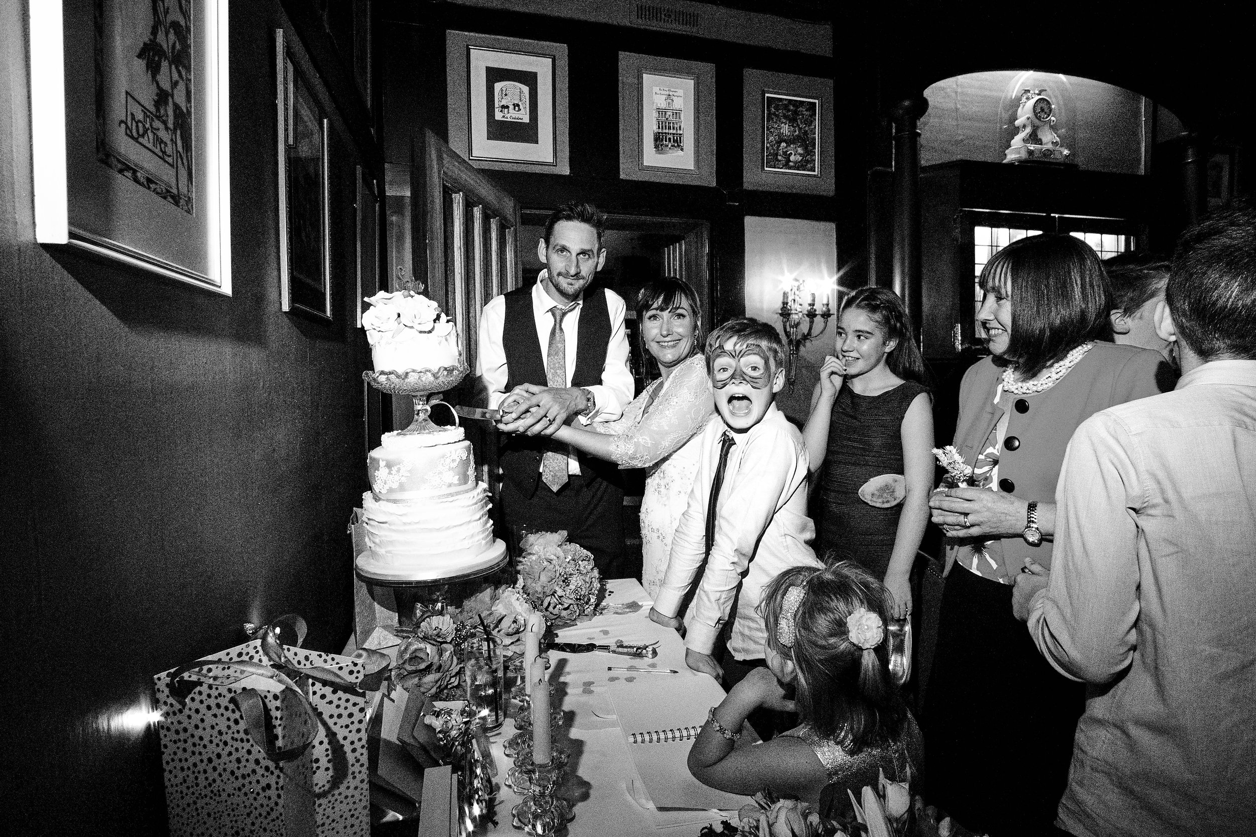 Cutting the cake, surrounded by family and friends - A Cheshire wedding at The Belle Epoque in Knutsford