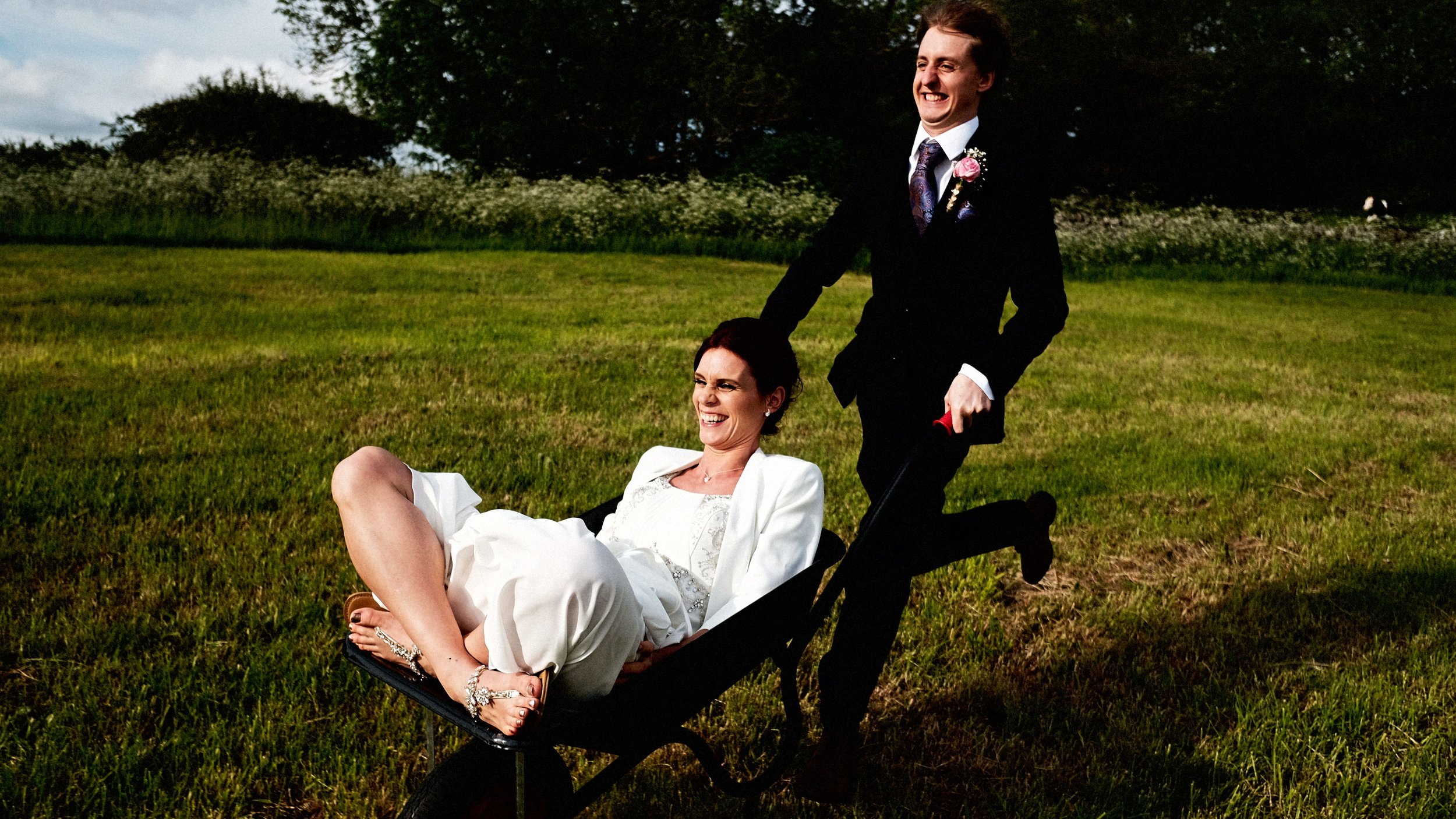 Bride and groom having incredible fun during their Rustic DIY Marquee Summer wedding in the Peak district.