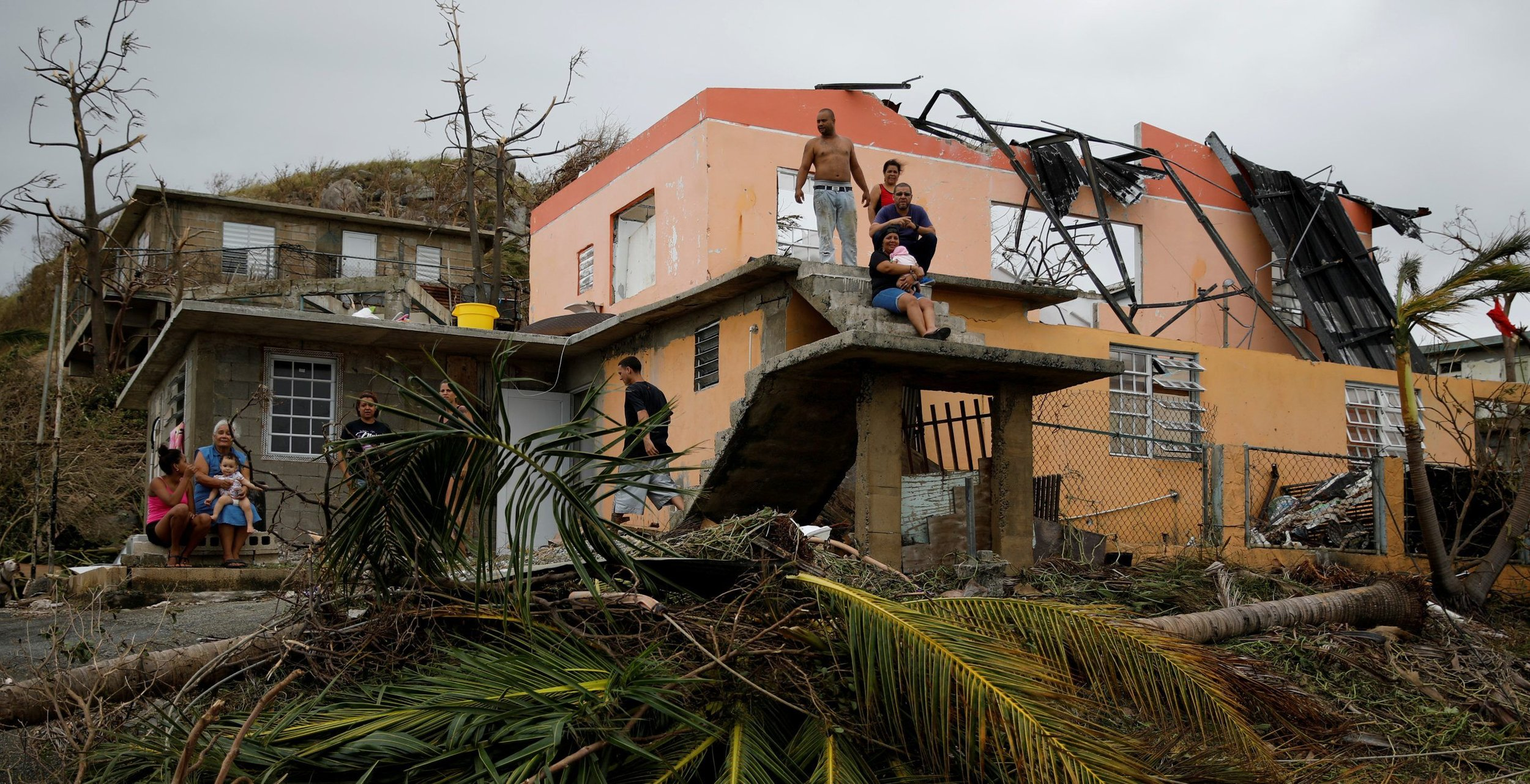 People rest outside a damaged house after the area was hit by Hurricane Maria in Yabucoa.