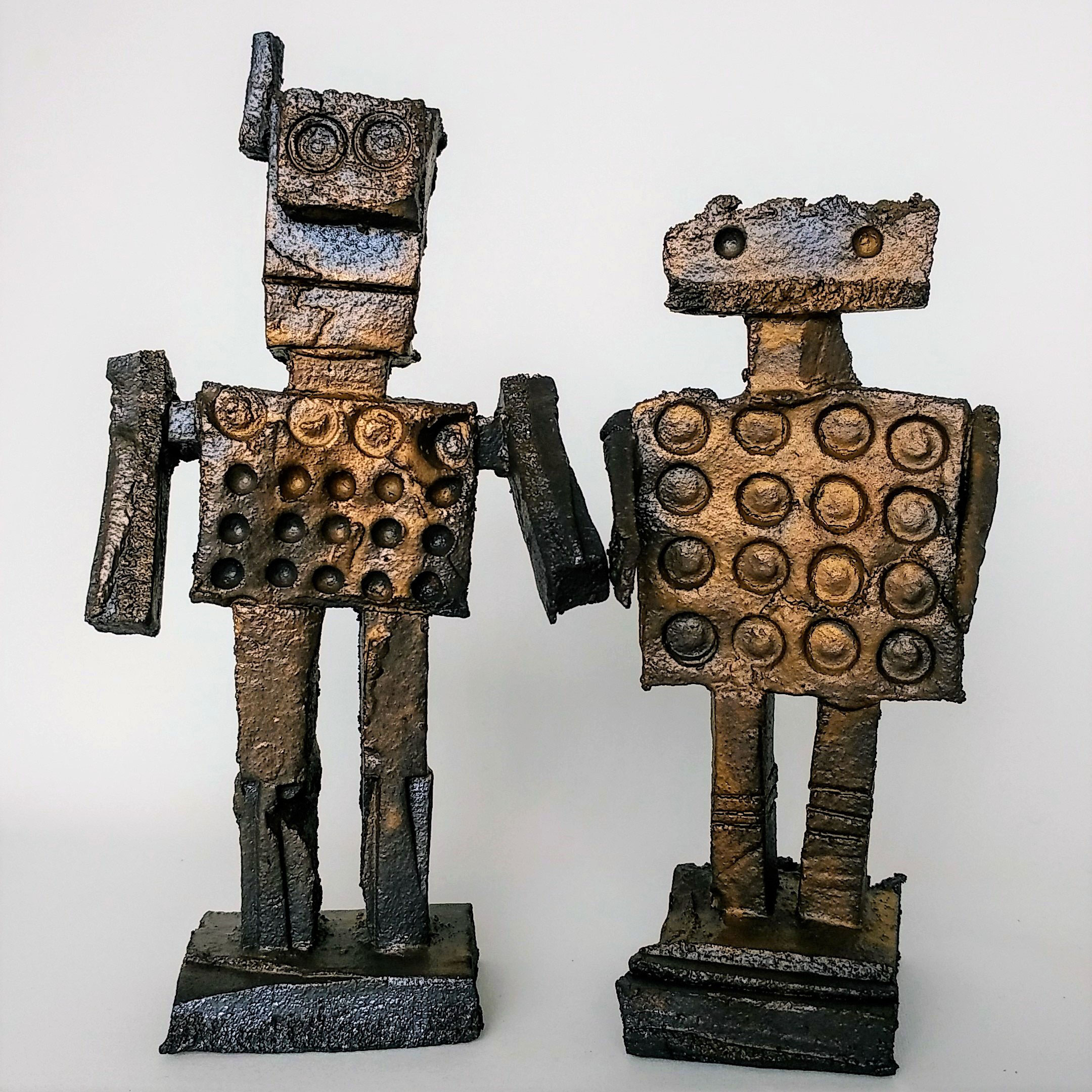 """Rough Robots   Mark Clough and Warren Dunn are art teachers near Manchester, Mark now retired. In addition to producing digital drawings, Mark and Warren got together to design rough robots, initially from cardboard, beachcombings and streetfinds, now from clay. What is universal across all their media is the recycling and incorporation into their images materials that have been jettisoned from a previous use. Robots are """"a modern archetypal form that can withstand all sorts of liberties of interpretation, but which can still be recognised."""" Among there influences they speak of """"the Japanese notion of flawed beauty ('wabi sabi'), the Golem legend, brutalism, industrial plant, tanks, aeroplanes, armour and Ned Kelly."""""""